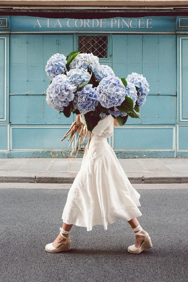 Out Of The Blue is a photo of a girl in Paris in St Germain des Prés holding the biggest bunch of baby blue hydrangeas and is part of a limited edition series named Young Girl in Bloom by photographer Carla Coulson celebrating women loving and believing in themselves and building their self esteem by trusting their intuition.