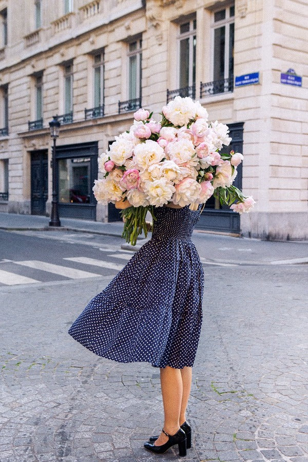 Standing Her Ground is a photo of a girl in Paris in St Germain des Prés holding the biggest bunch of ancient white peonies and is part of a limited edition series named Young Girl in Bloom by photographer Carla Coulson celebrating women loving and believing in themselves and building their self esteem by trusting their intuition.