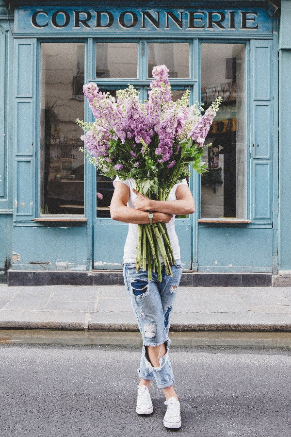 I Saw You Standing There is a photo of a girl in Paris in Le Marais holding a bouquet of purple delphiniums and is part of a limited edition series named Young Girl in Bloom by photographer Carla Coulson celebrating women loving and believing in themselves and building their self esteem by trusting their intuition.