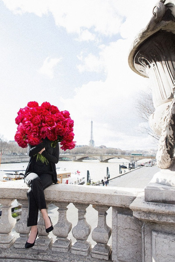 girl sitting on post alexandre III in Paris with a giant bouquet of red peonies with Eiffel Tower in the background