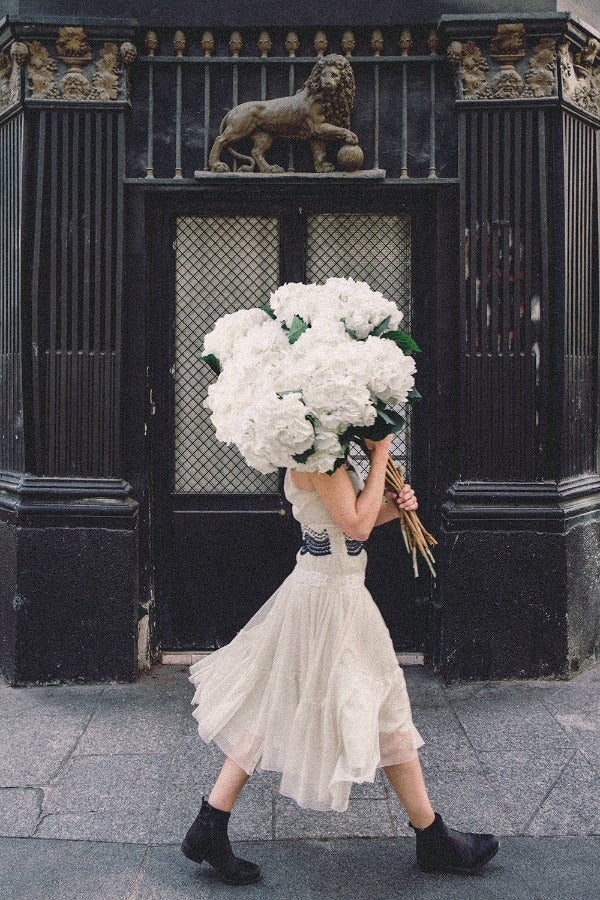 Going Places is a photo of a girl in the 10th Arrondissement in Paris with a big beautiful bunch of white hydrangeas and is part of a limited edition series named Young Girl in Bloom by photographer Carla Coulson celebrating women loving and believing in themselves and building their self esteem by trusting their intuition.