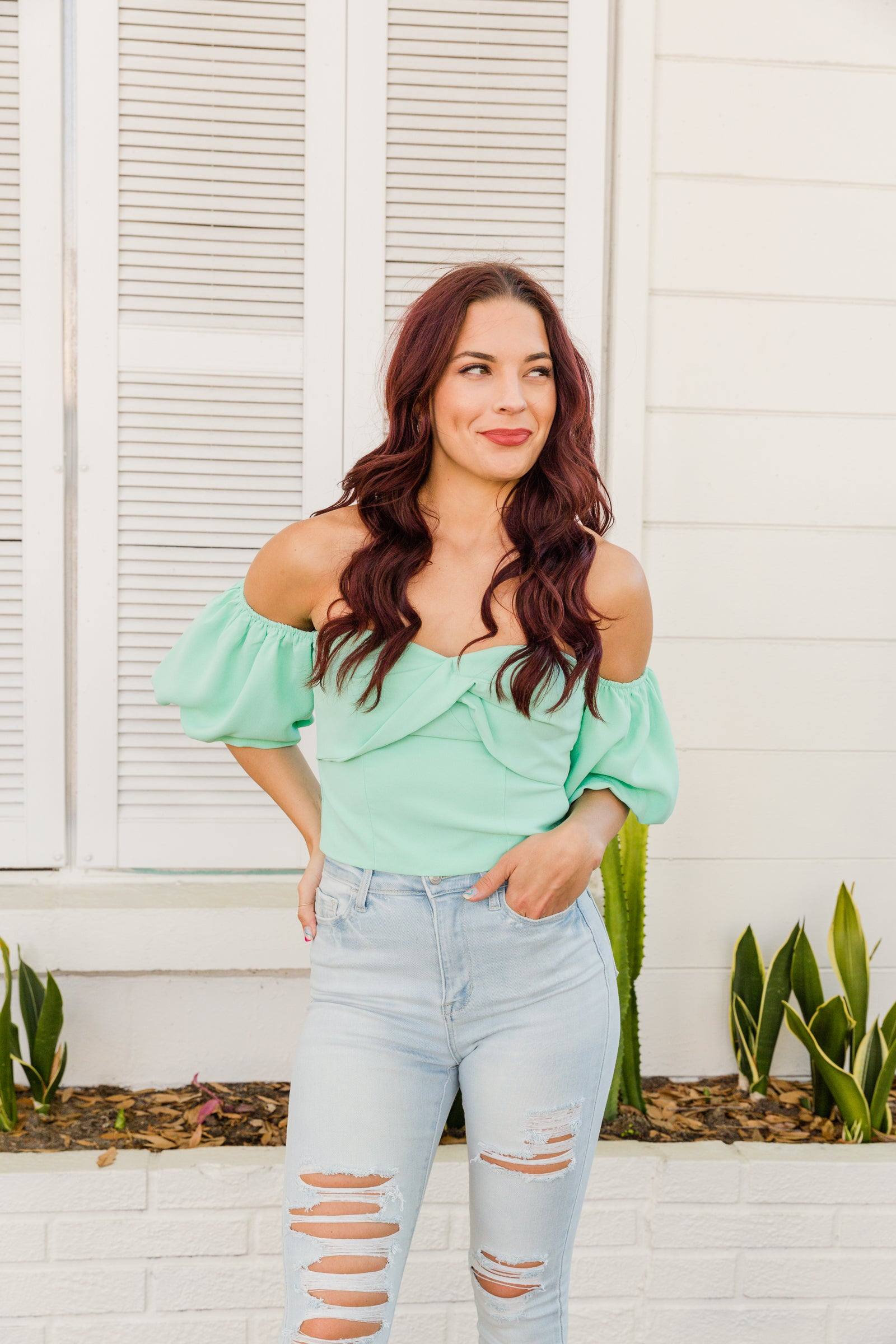 Short elastic cuffed bubble sleeves attach to an off-the-shoulder bodice with a sweetheart neckline, bust twists, and gathers before smoothing out into a cropped bodice silhouette with a smocked back.