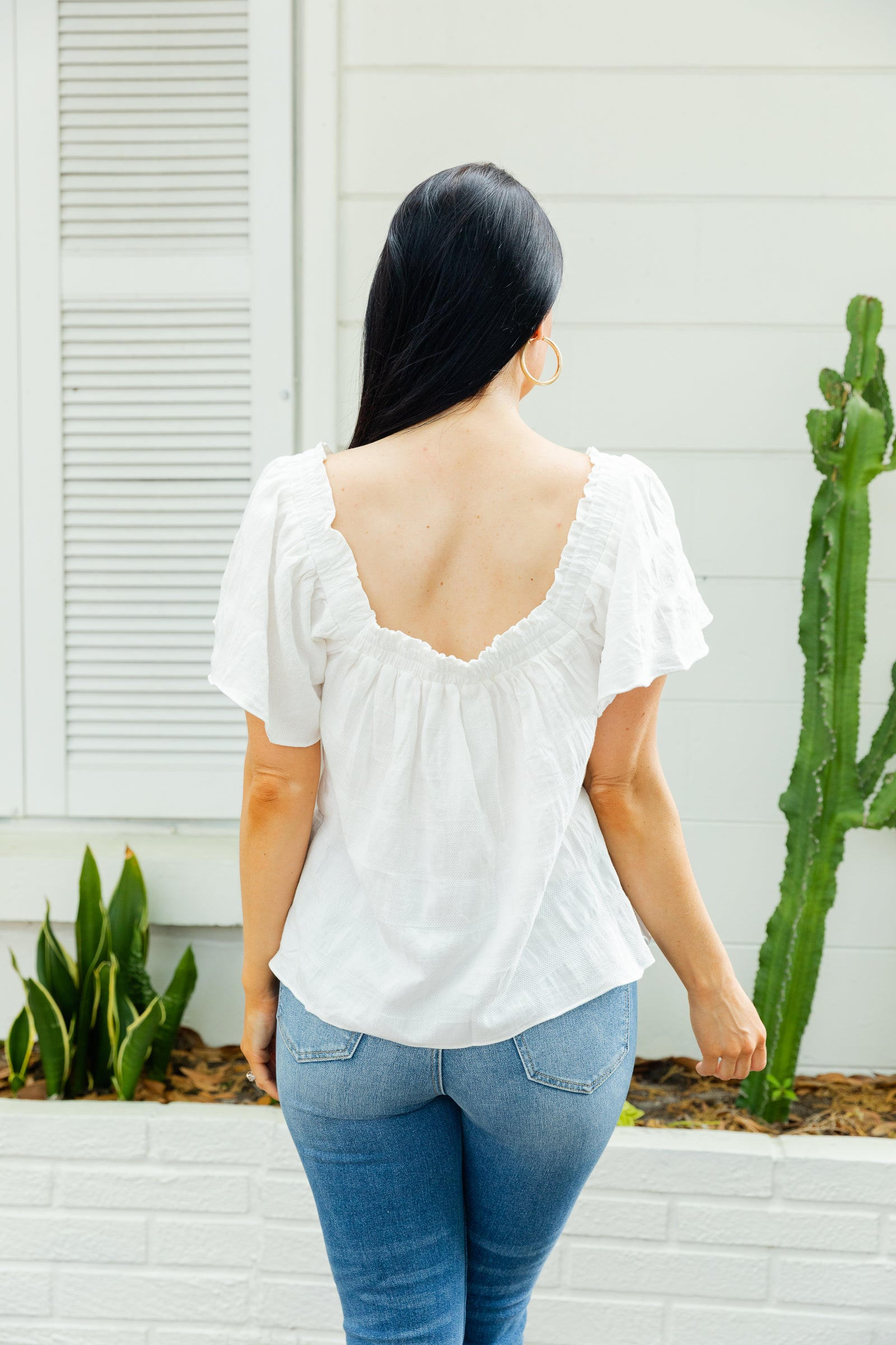 This lightweight top has short loose sleeves that attach to an off-the-shoulder and straight ruffled neckline on a flowy and oversized bodice silhouette.