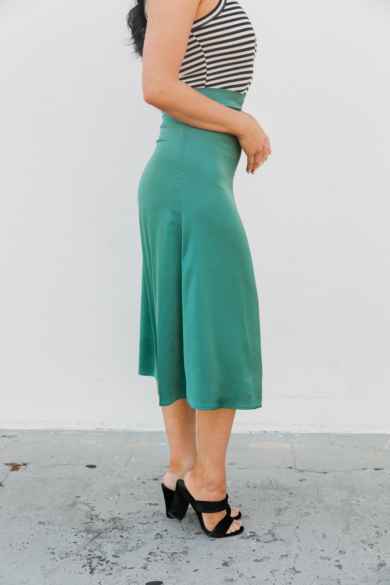 This satiny skirt has a fitted waistband with a zipper at the side that leads into a fitted then flowy skirt silhouette that meets mid-calf. Style this spring midi skirt with a bodysuit.