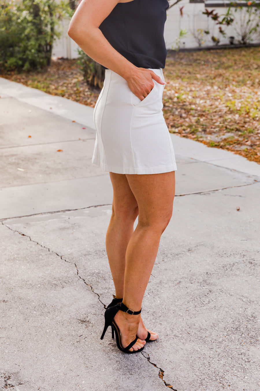 This white skirt has a fitted waistband that is buttoned and has a zipper fly on a paneled and fitted mini skirt. This denim mini skirt features side pockets.