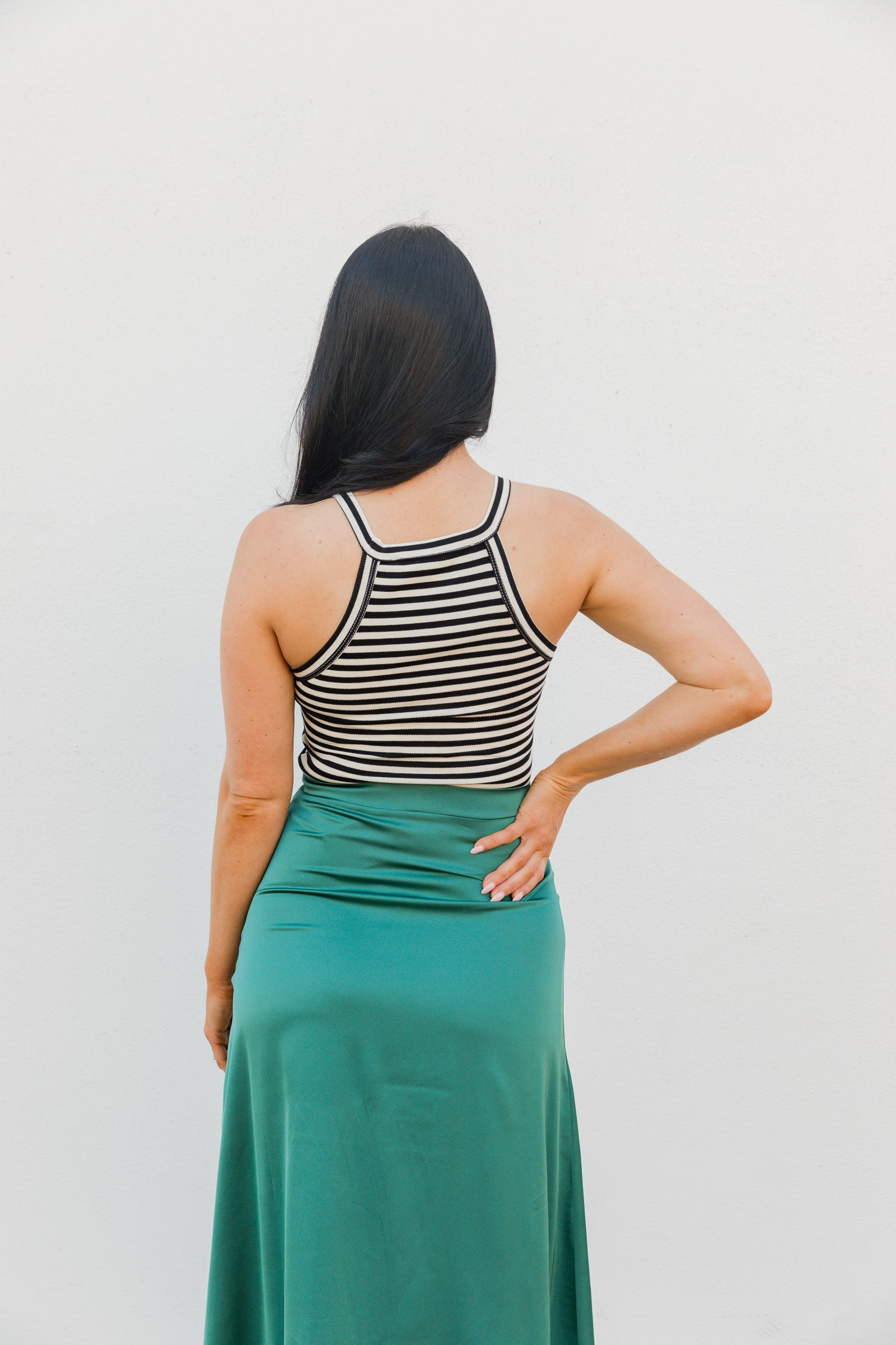 Black and white stripes run across this darling top. It is sleeveless with a high banded u-neckline, with banded armholes on a ribbed and cropped bodice.