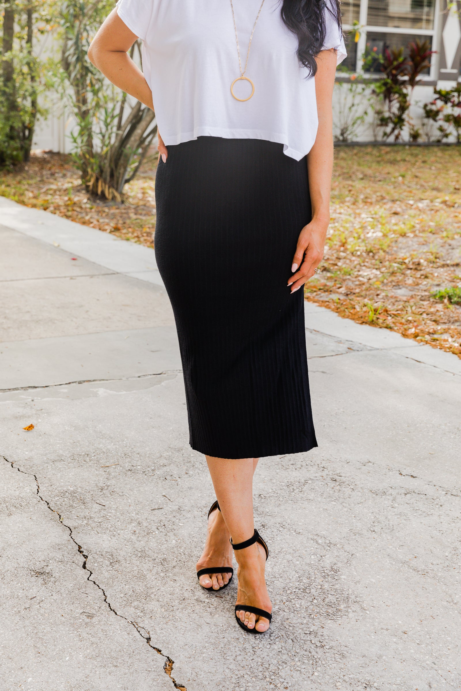 Elastic waistband on a fitted and hip-hugging pencil skirt silhouette with a slit down the side. Style this bodycon midi skirt with a bodysuit, block heels, and statement clutch.