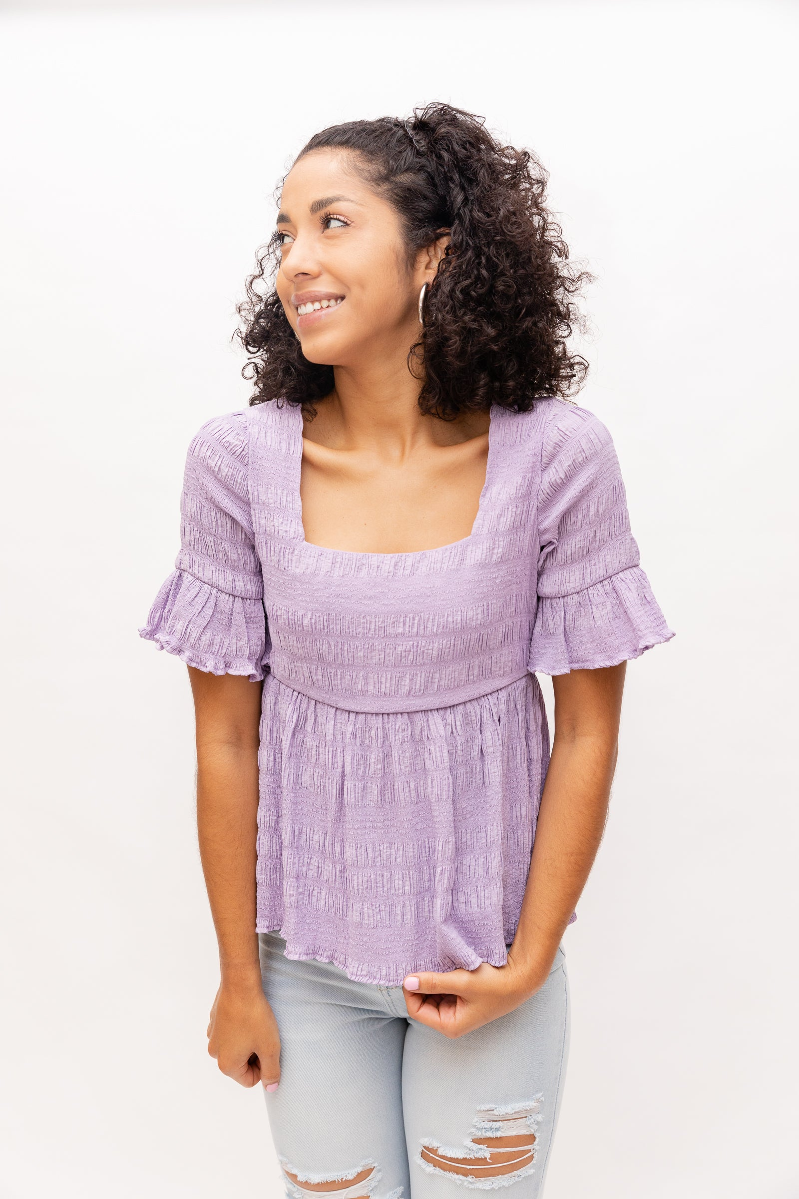 Short ruffle cuffed sleeves attach to a fitted neckline on a textured and relaxed bodice before flaring out into a baby doll peplum hem.