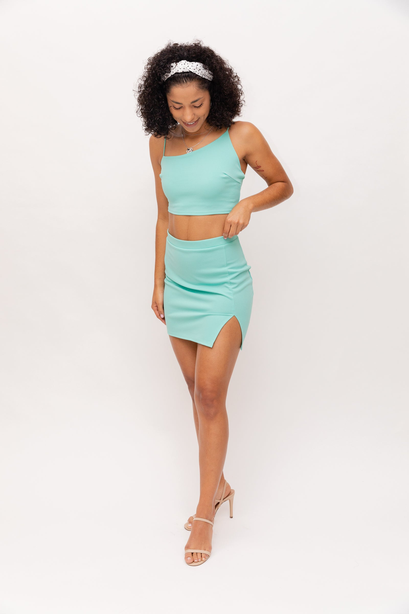 It has an elastic waistband and goes into a mini and fitted tube pencil skirt with a slit at the side. Style this spring skirt with the Landon One Strap Crop Top.