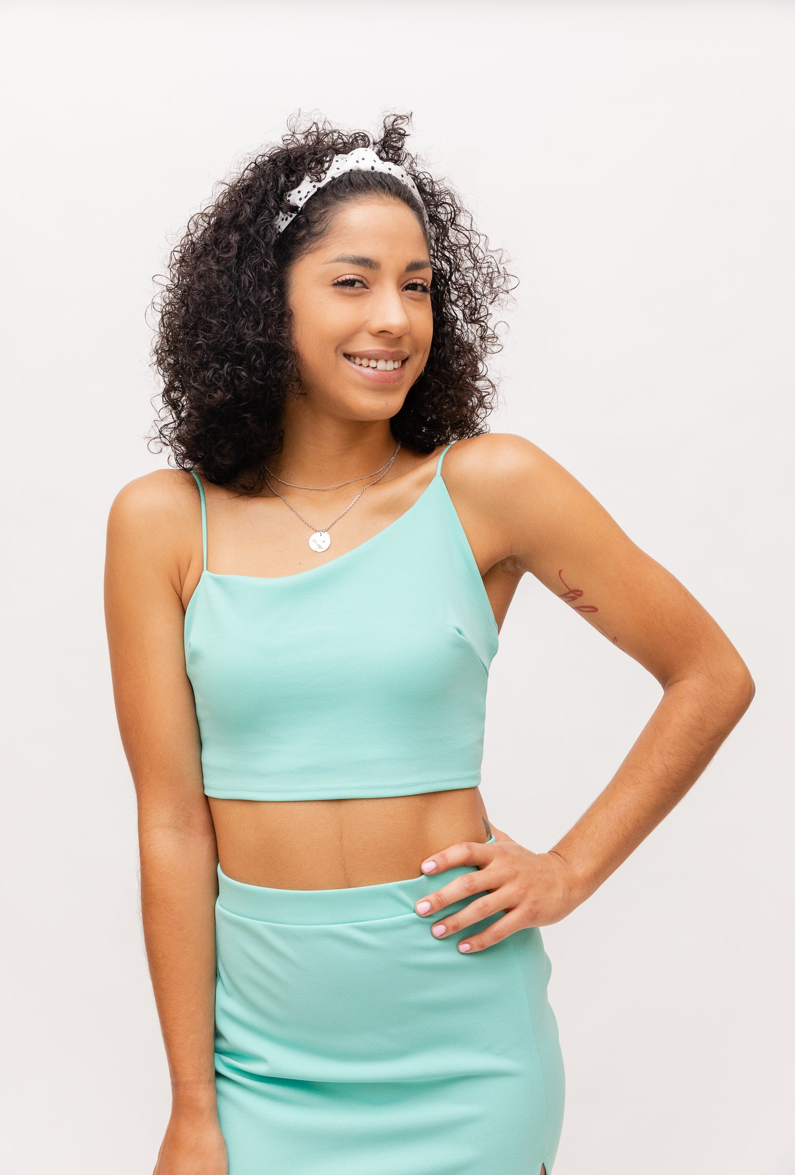This spring top has bungee straps with one main strap that goes across the neckline asymmetrically on its fitted and cropped bodice.