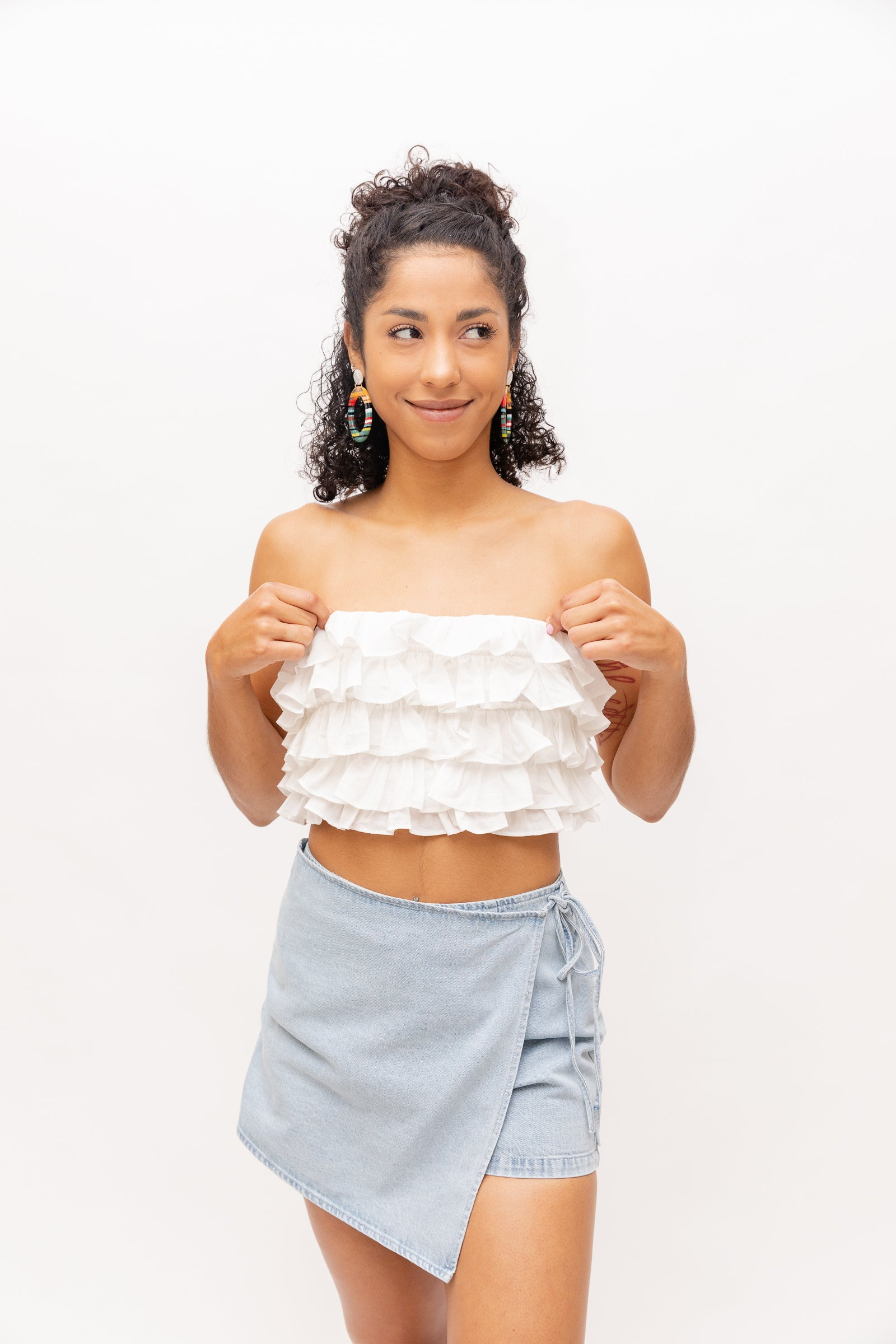 This strapless crop top has a layered ruffle trim down the bodice and on the back is crisscrossed and tied down the center.
