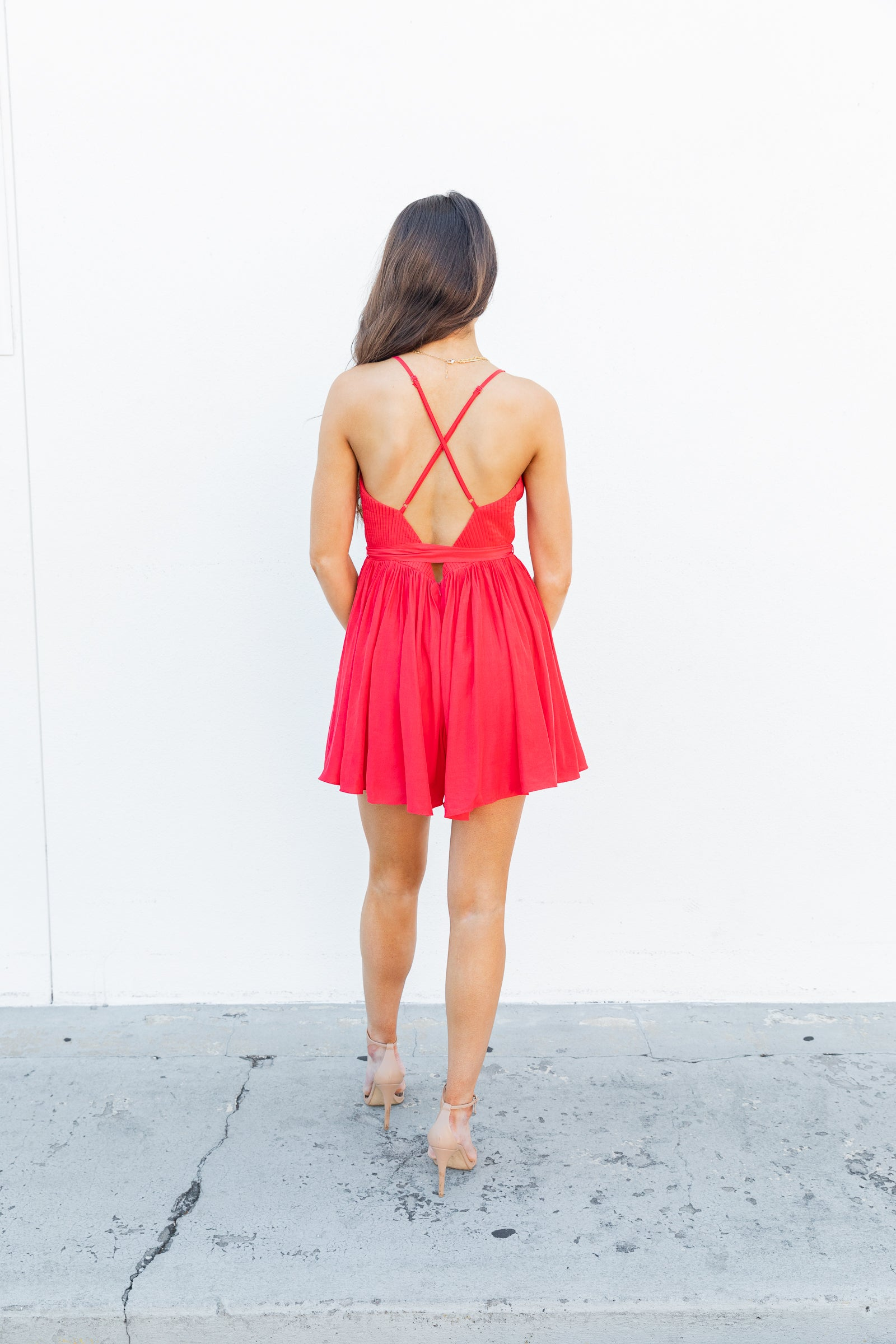 Thin straps attach to a v-neckline on a pleated and paneled bodice and meets a fitted wait before flowing to loose and comfortable shorts. This red romper features a fabric belt to cinch at the waist.