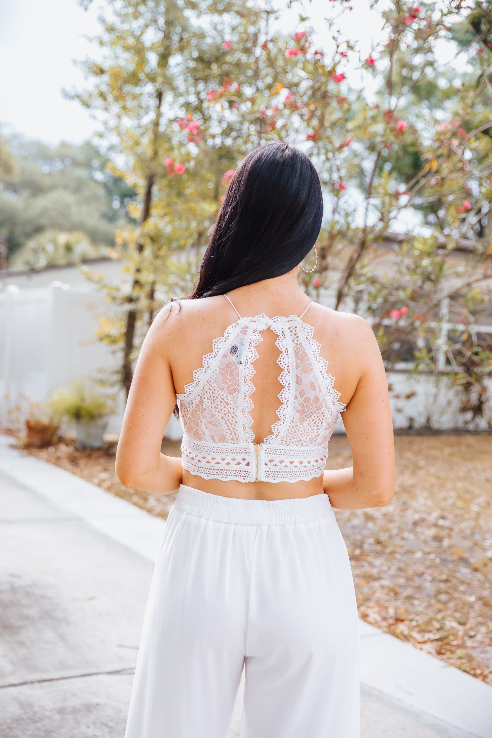 Thin bungee straps attach to a high laced-trim neckline on a cropped bodice with crochet-centered detail meeting with laced panels, has a crochet waistband and a keyhole opening on the back.