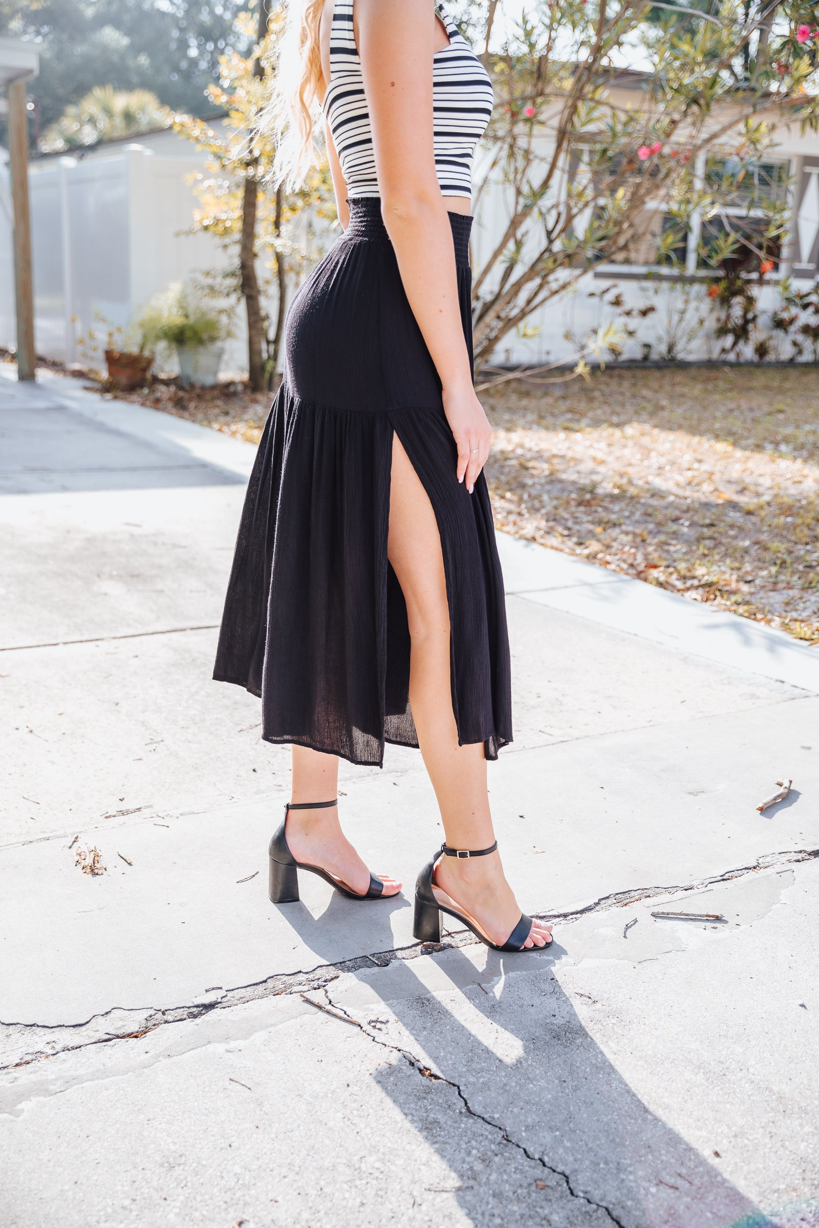 This black skirt has a thick smocked waistband and flows down into a tiered hem with slits at the side. Style this lightweight maxi skirt with a bodysuit.