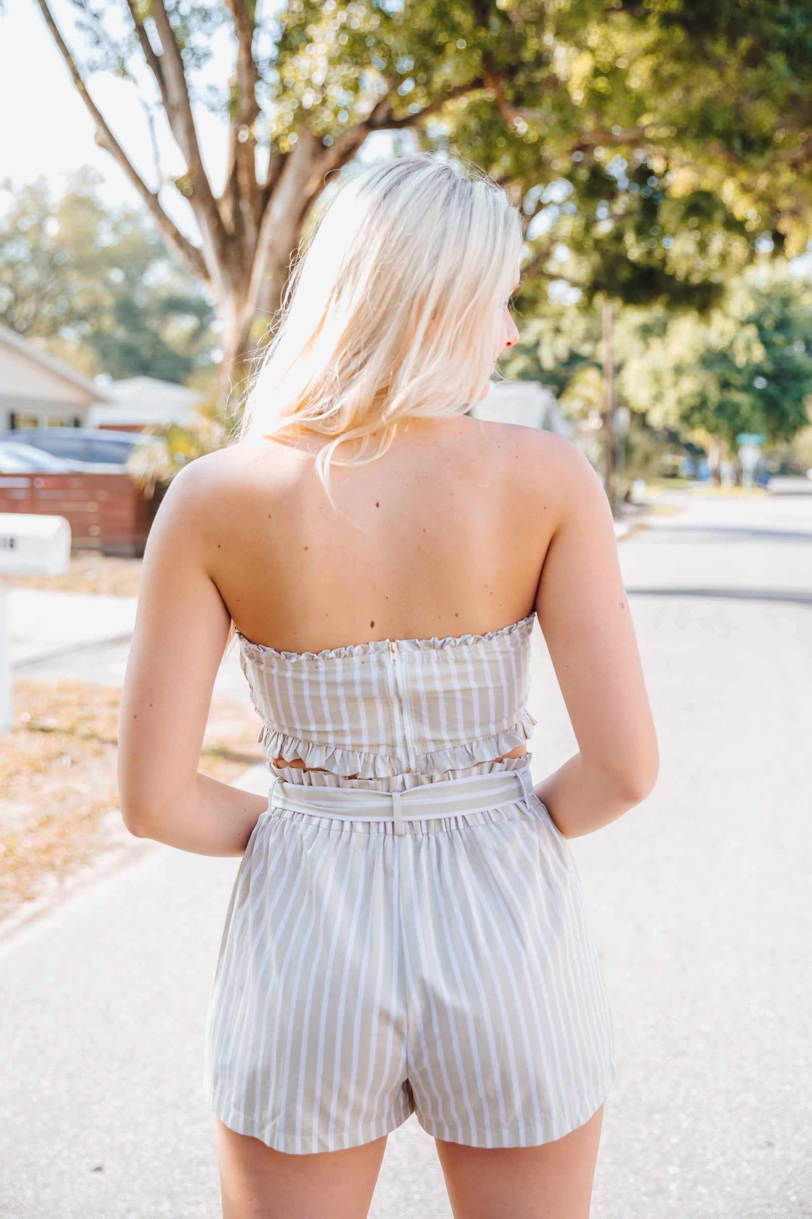 This crop top has white stripes that go across its fabric. It is strapless with a straight neckline on a smocked bodice with button details down the center and ends in a small ruffle-trimmed hem.