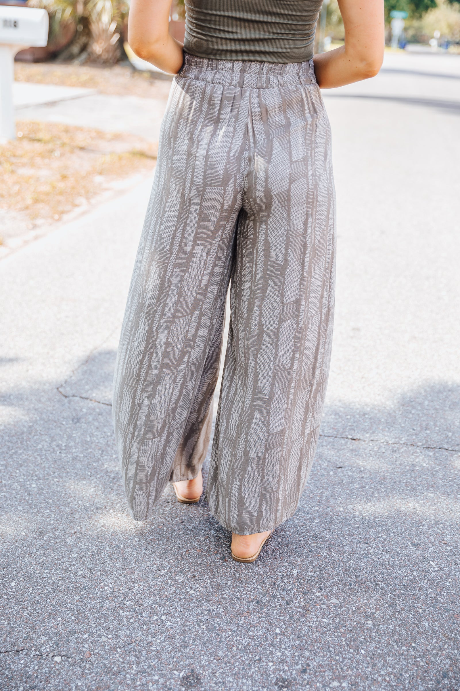 White prints cover the fabric of these lightweight pants. It has an elastic waistband meeting side panels that ties in the front and then flows into long and wide pant legs.