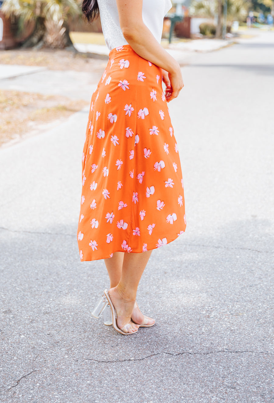Pink floral prints cover the fabric of this lightweight tulip midi skirt. It has a fitted waistband that meets button details on the side of an asymmetrical high-low skirt hem.