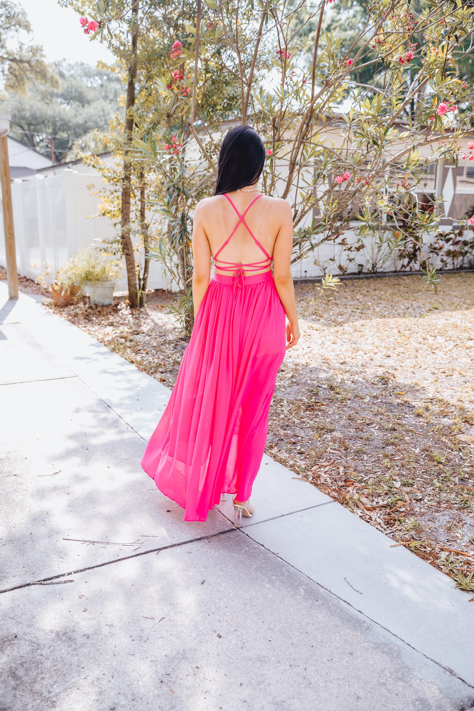 Skinny adjustable straps attach to a deep v-neckline on a triangle bodice with cutouts at the side. It meets a fitted waistband and flows down into a long chiffon maxi skirt with slits.