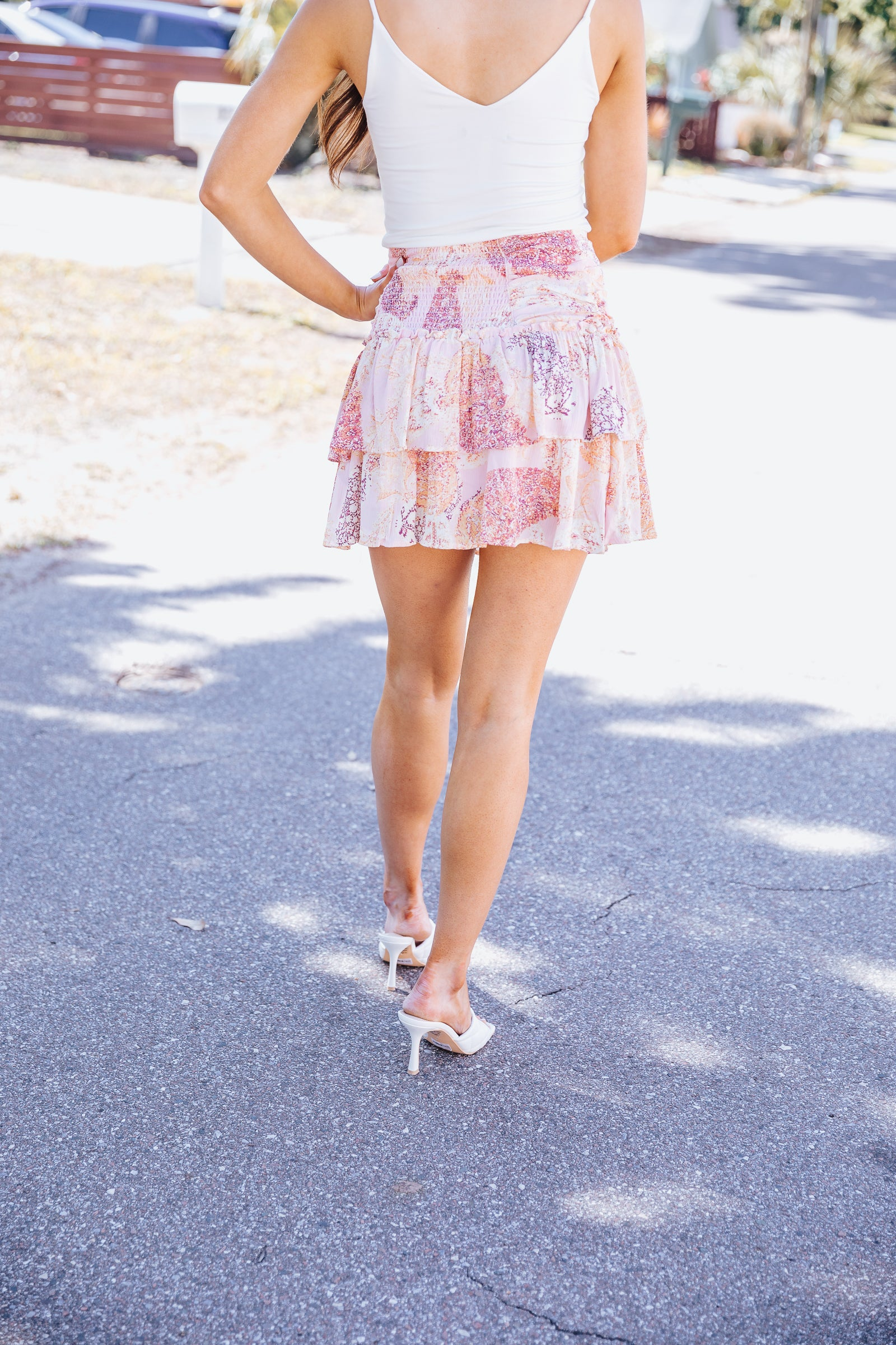 This patterned mini skirt has a gathered and gently ruched waist and meets a layered and ruffle hemmed silhouette.