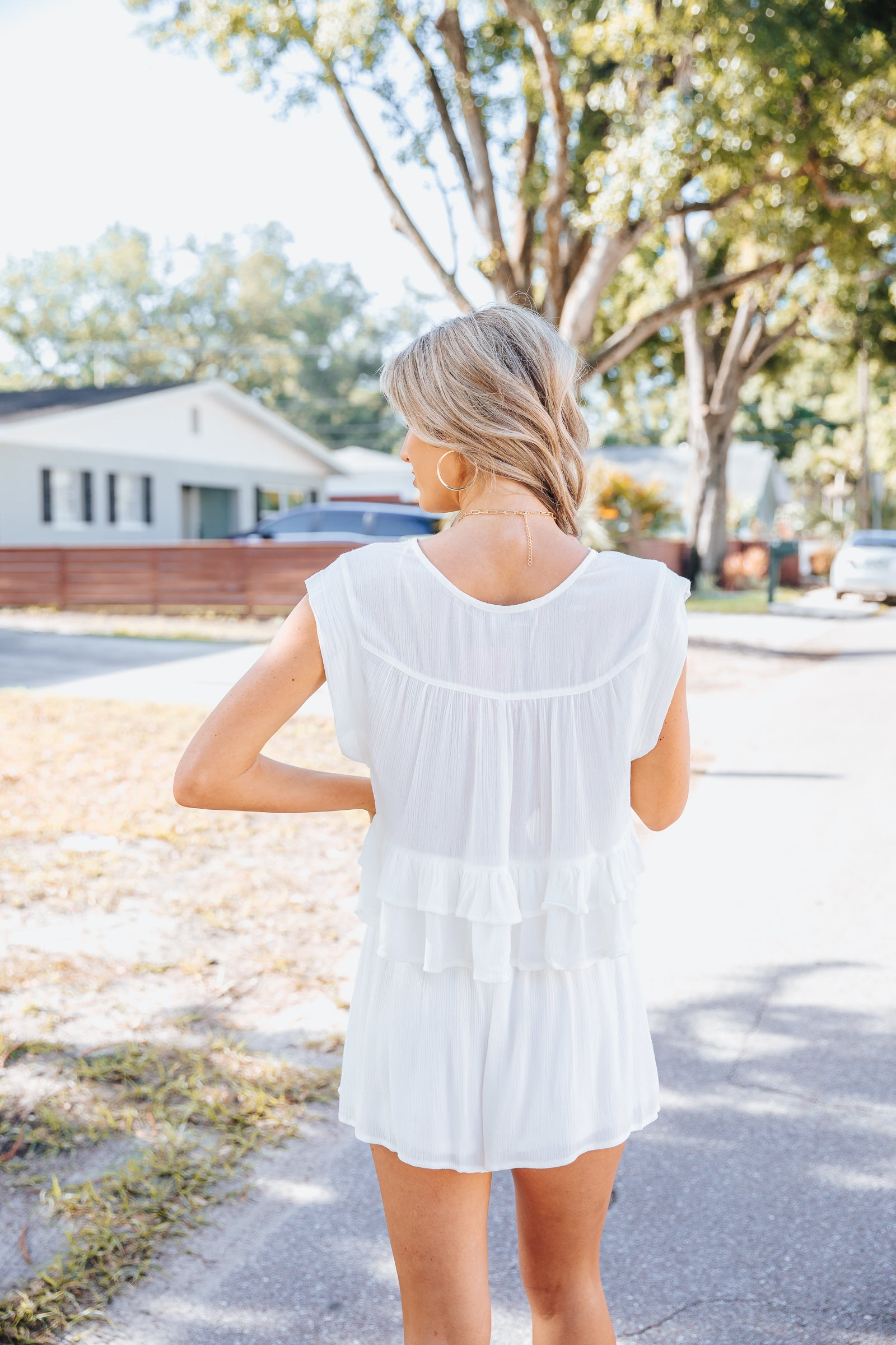 This sleeveless crop top has a notched deep v-neckline on a relaxed bodice with a button-down center. It has pleated panels that meet a layered and ruffle hem at the bottom of its cropped bodice.