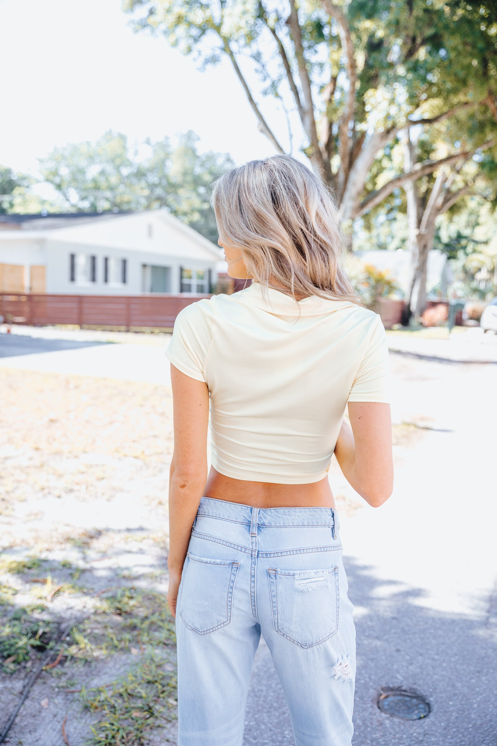 Short sleeves attach to a collared and v-neckline on a ruched centered bodice that is fitted and cropped. Style this shiny crop top with high-rise jeans.