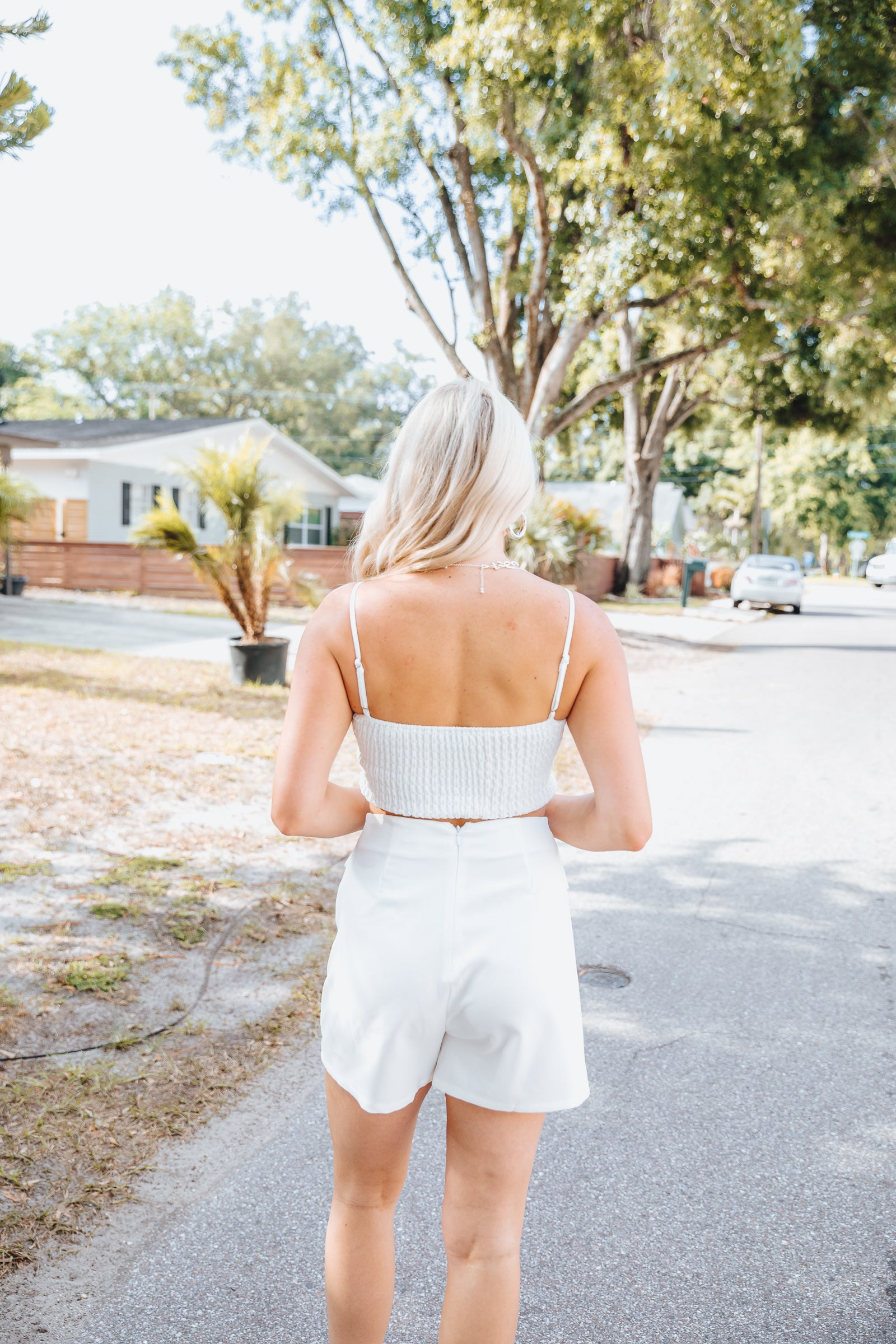Thin adjustable straps attach to a notched neckline on padded cups on a fitted and cropped bodice. Style this white crop top with the Meena Skort.