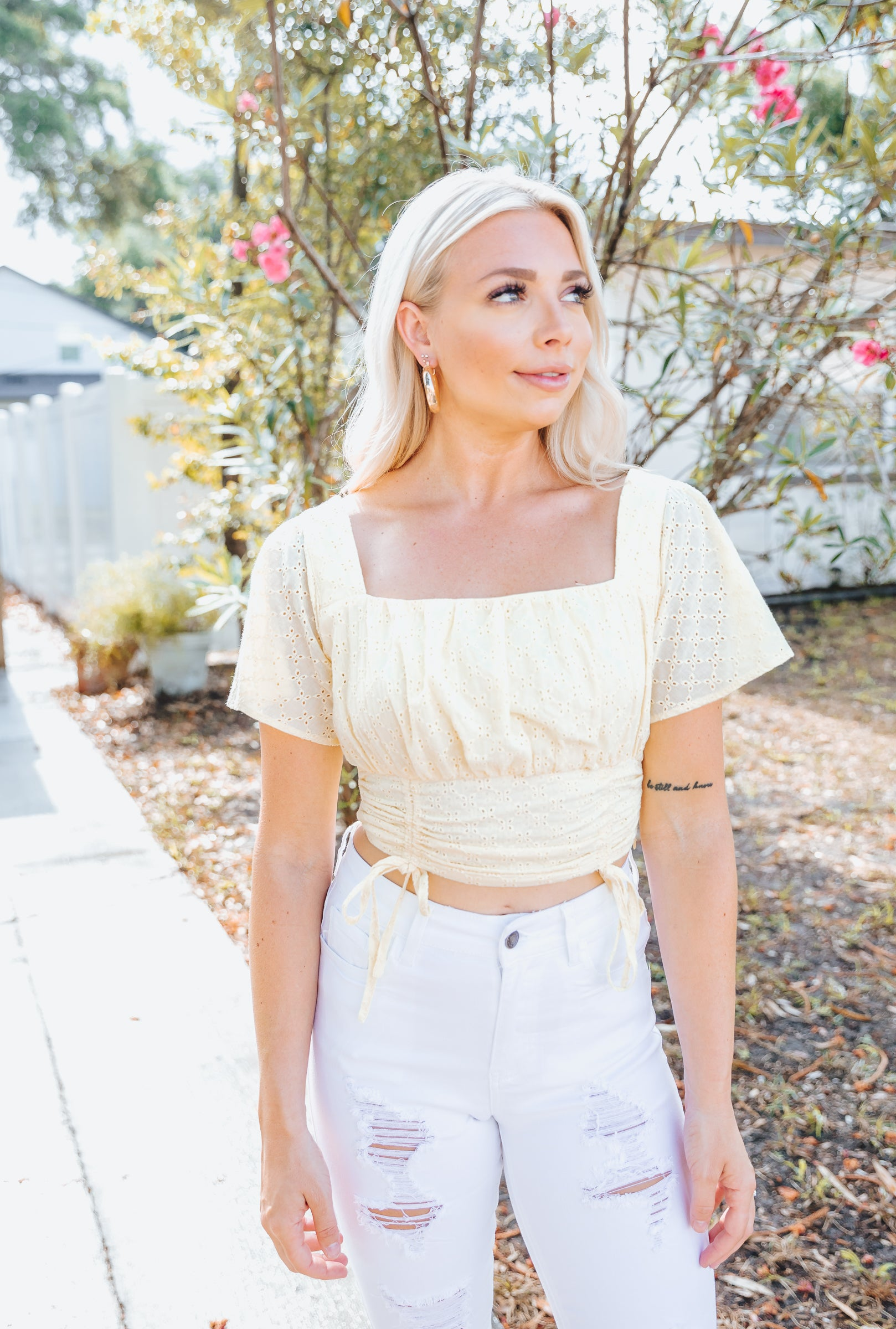 Short sleeves attach to a square neckline on a shirred bust on a fitted and cropped bodice. Style this spring crop top with a skort.