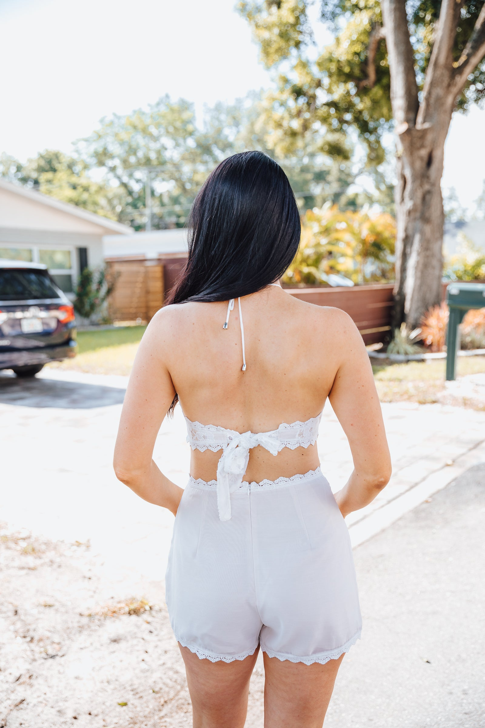 Lace overlay goes over an opaque nude fabric. It has medium straps on a high banded neckline and goes into a sleeveless and fitted bodice that is tied on the back.
