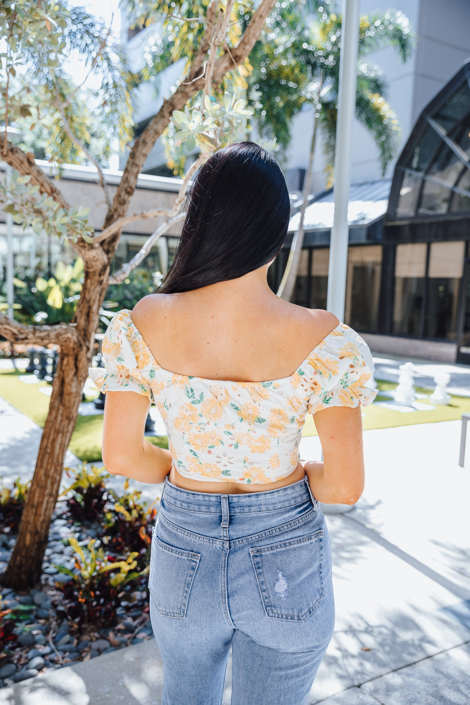 Yellow floral prints cover the eyelet fabric of this top. It has short ruffle cuffed sleeves that attach to a v-neckline with a center ruched and fitted bodice.