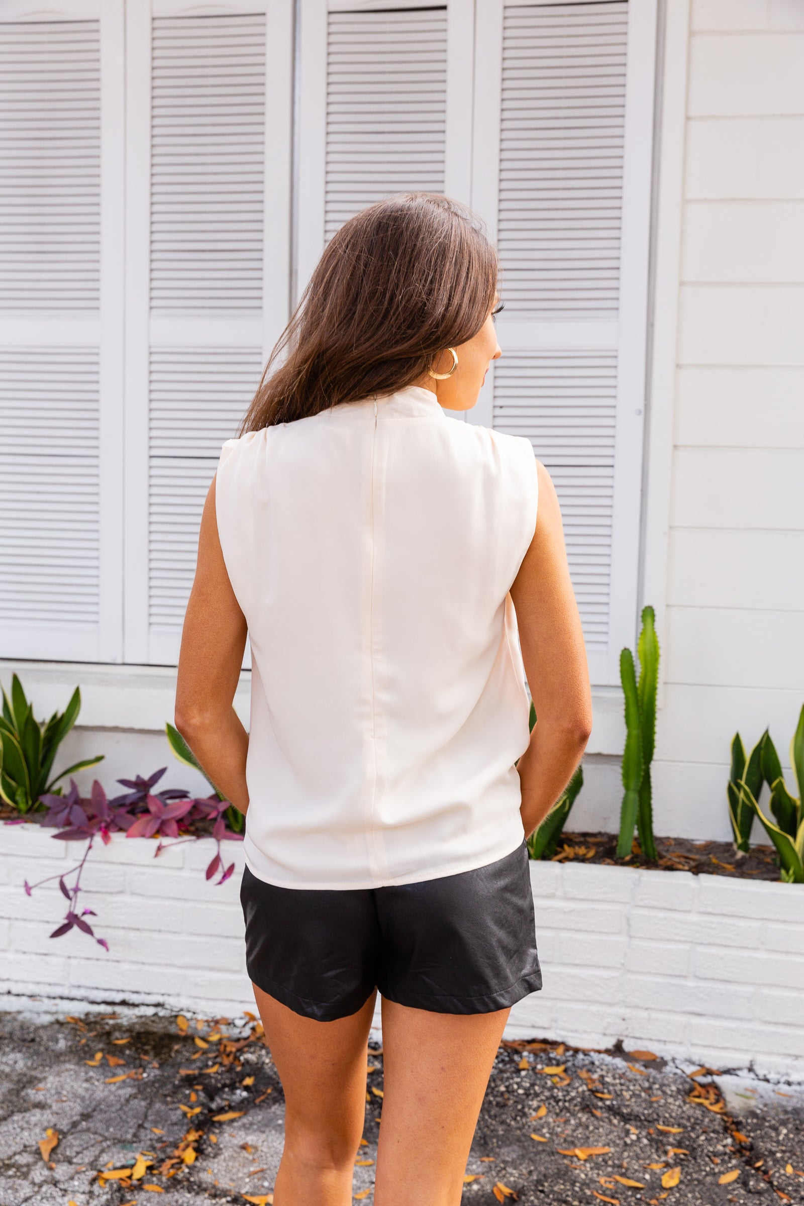 This sleeveless blouse has a loose mock neckline and a relaxed and flowy fit finishing with a clean hem. This lightweight top features a zipper with a hook and eye closure on the back of the neck.