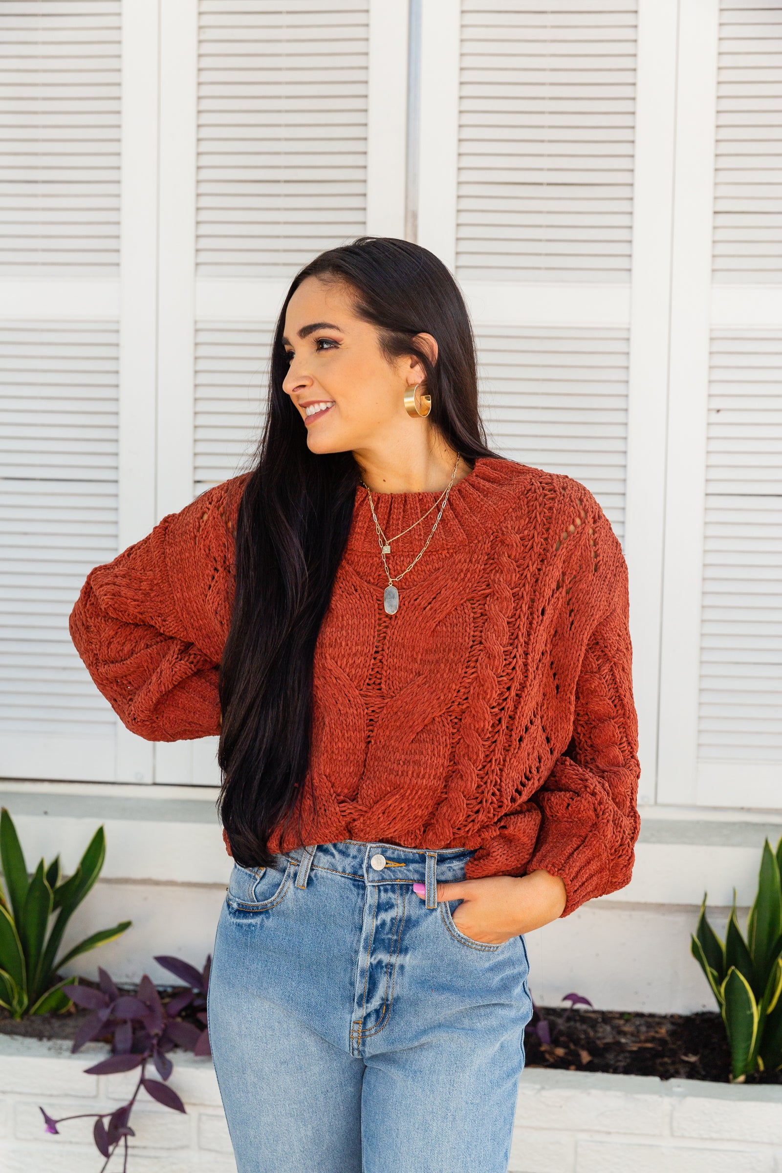 This cable knit sweater has long bishop sleeves that attach to a banded u-neckline on an oversized and relaxed bodice silhouette.