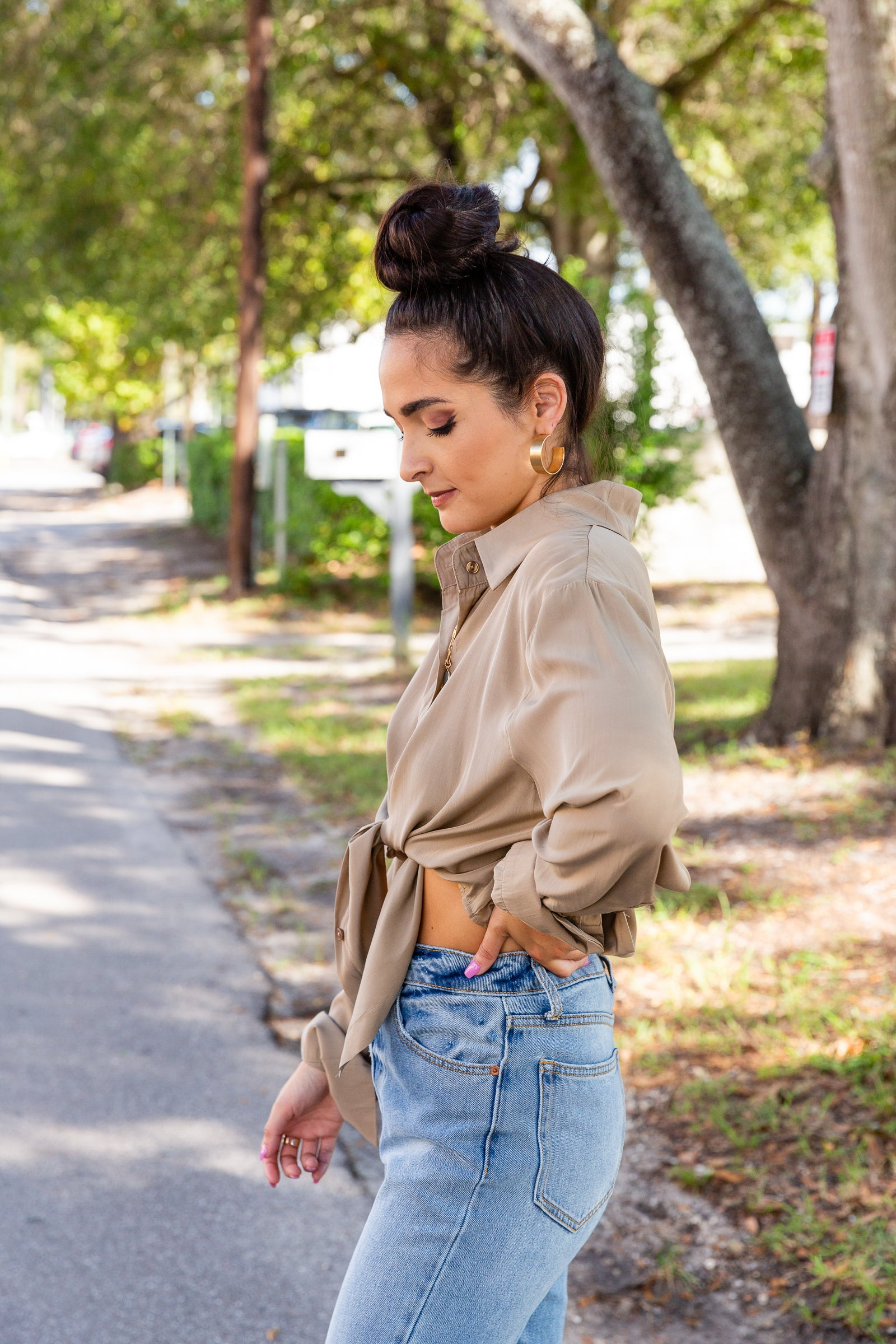 Long button cuffed sleeves that attach to a collared v-neckline with a button-down front and a cropped and relaxed silhouette meeting a hem that could be tied in the front or worn loosely.