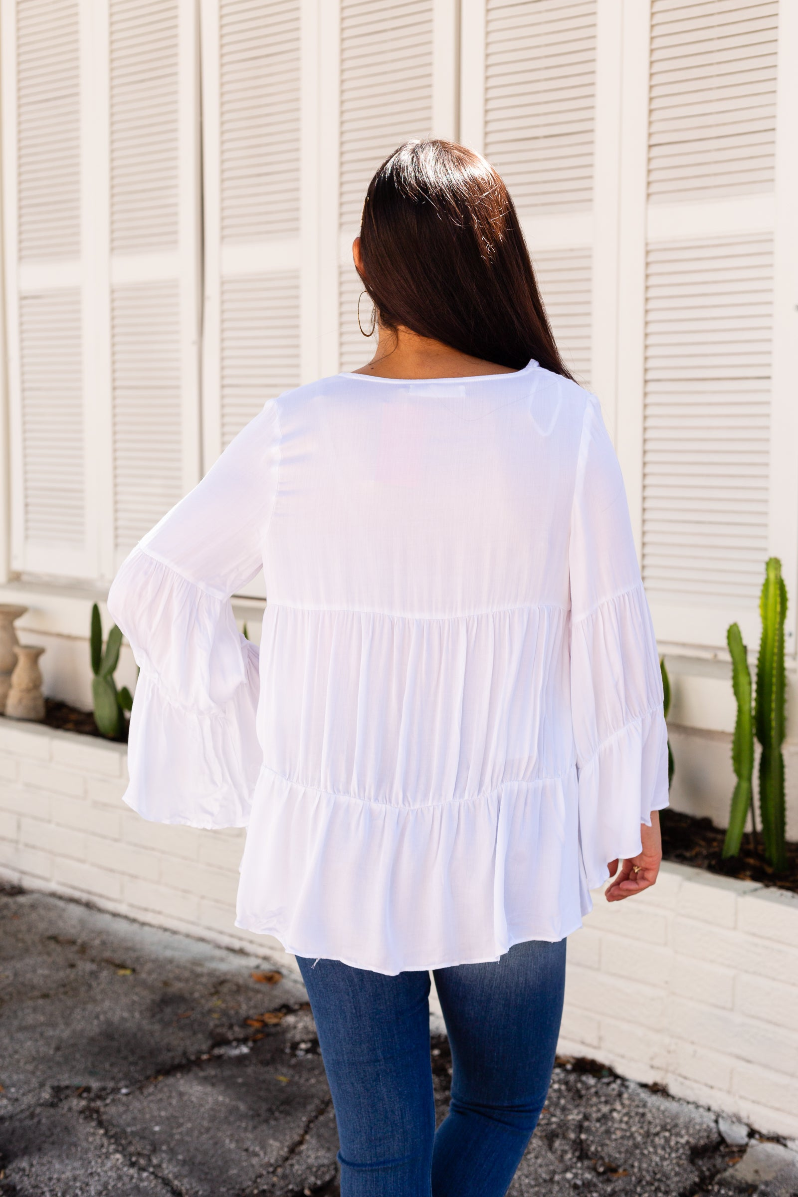 Long bell-sleeves attach to a v-neckline on an oversized and loose tiered bodice. Style this lightweight top with your favorite medium-wash jeans.