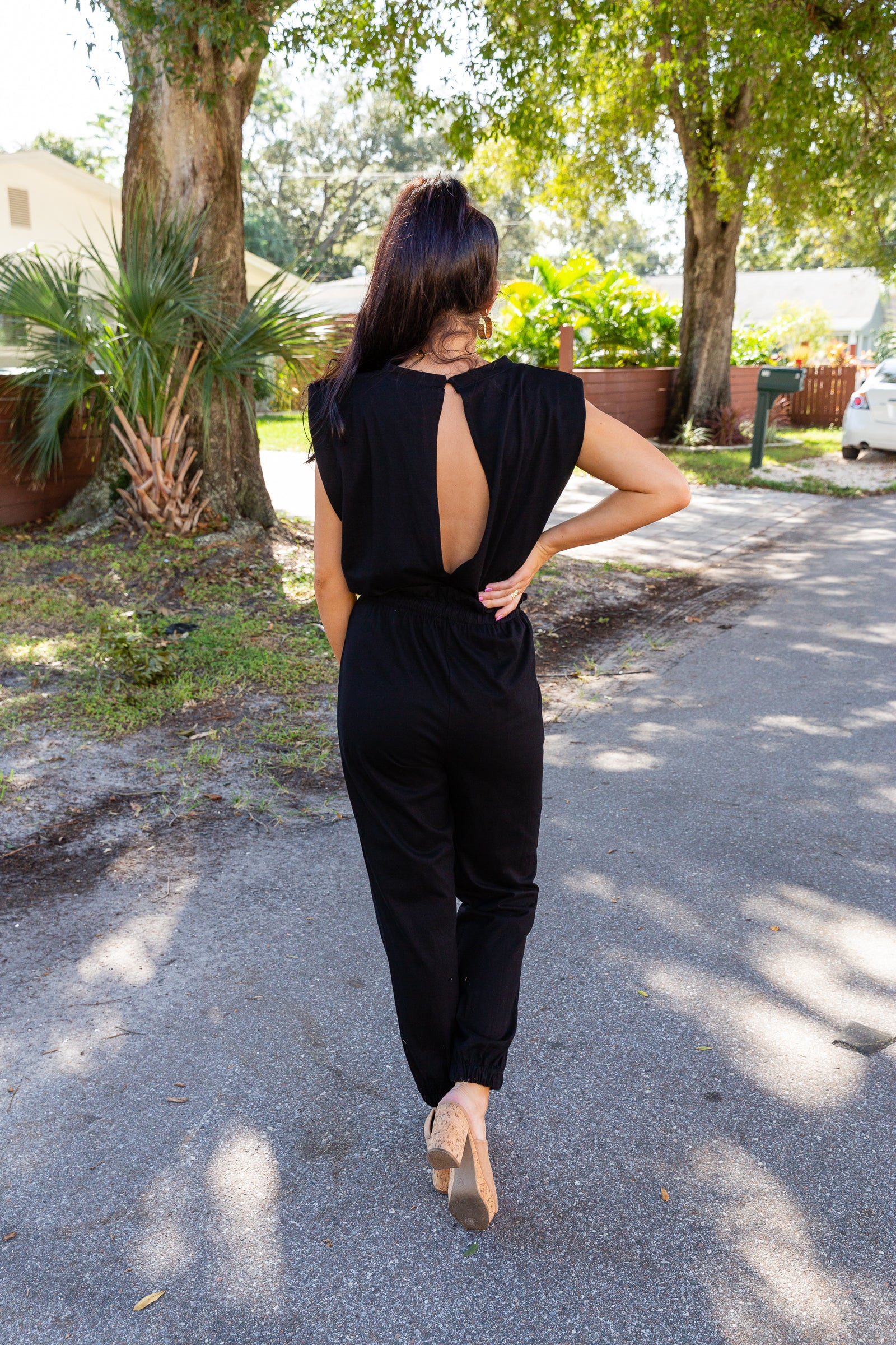 This sleeveless jumpsuit has shoulder pads next to a u-neckline on a relaxed fit bodice before meeting a drawstring waist and goes into straight pantlegs with an elastic ankle cuff.