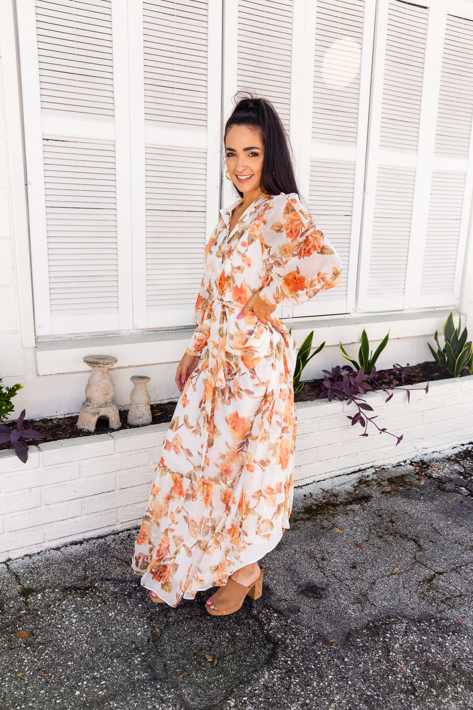 Long button cuffed sleeves that attach to a collared neckline on a button-down silhouette. The relaxed bodice leads to a long flowy skirt with a ruffle hem at the bottom.
