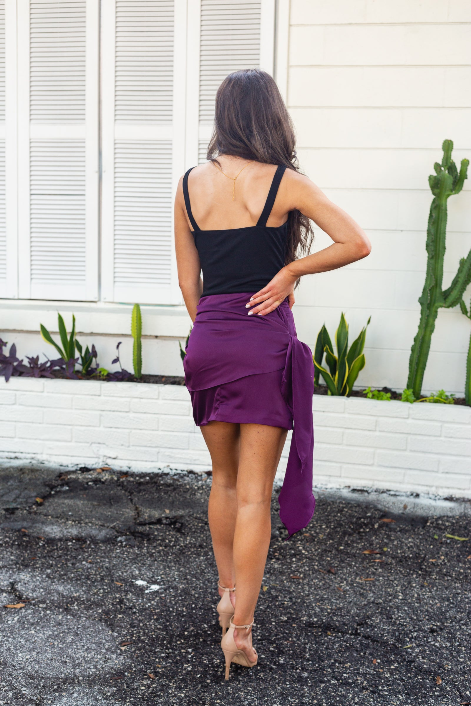 This adorable skirt has a fitted waistband and goes down into a side-tied drape with a ruched side detail on the opposite side. This drape sits atop a simple straight mini skirt silhouette.