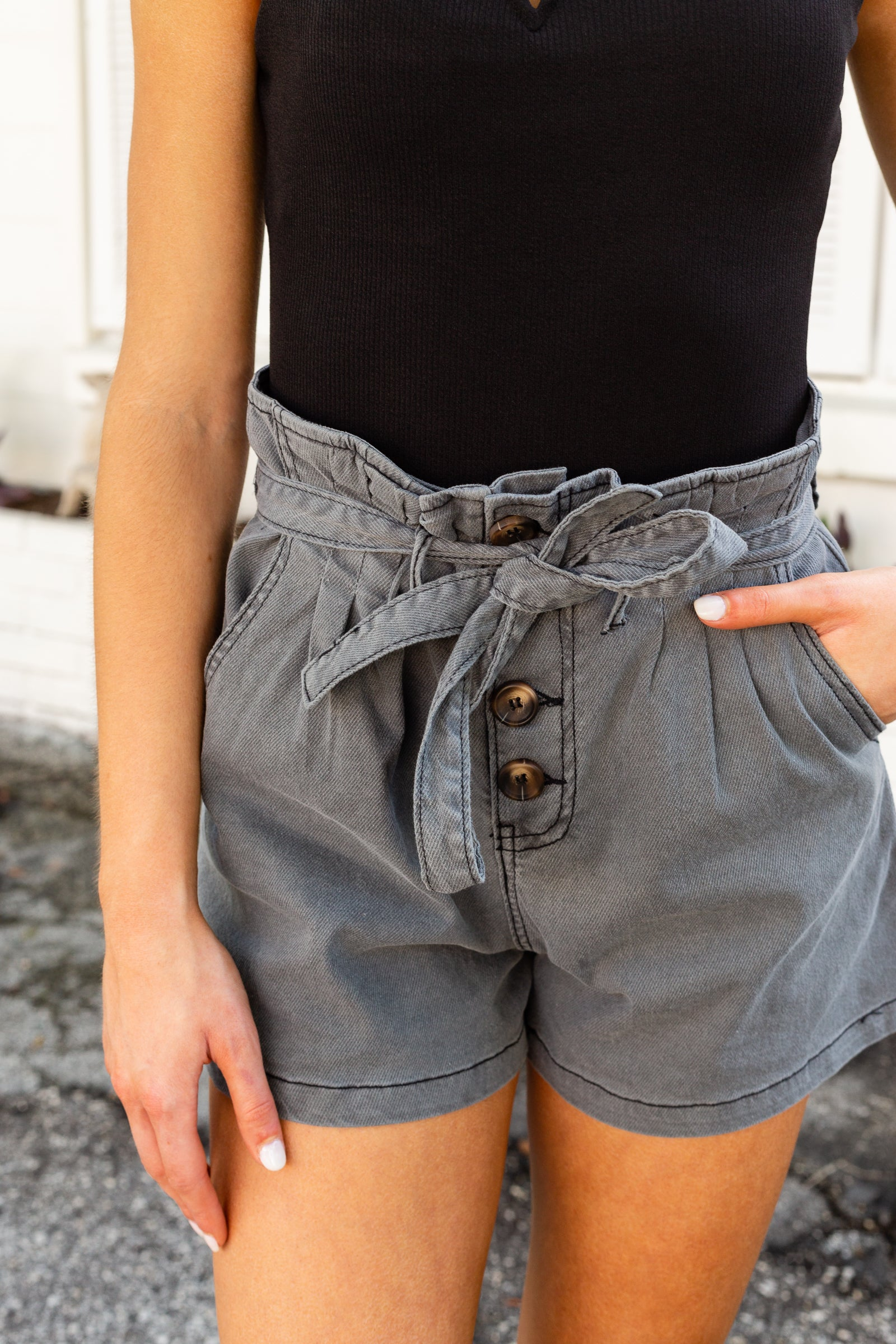 Fitted paper bag style waistband with belt loops lead to a button-down detailed fly and goes down to a traditional 4-pocket structure into relaxed-fit shorts.