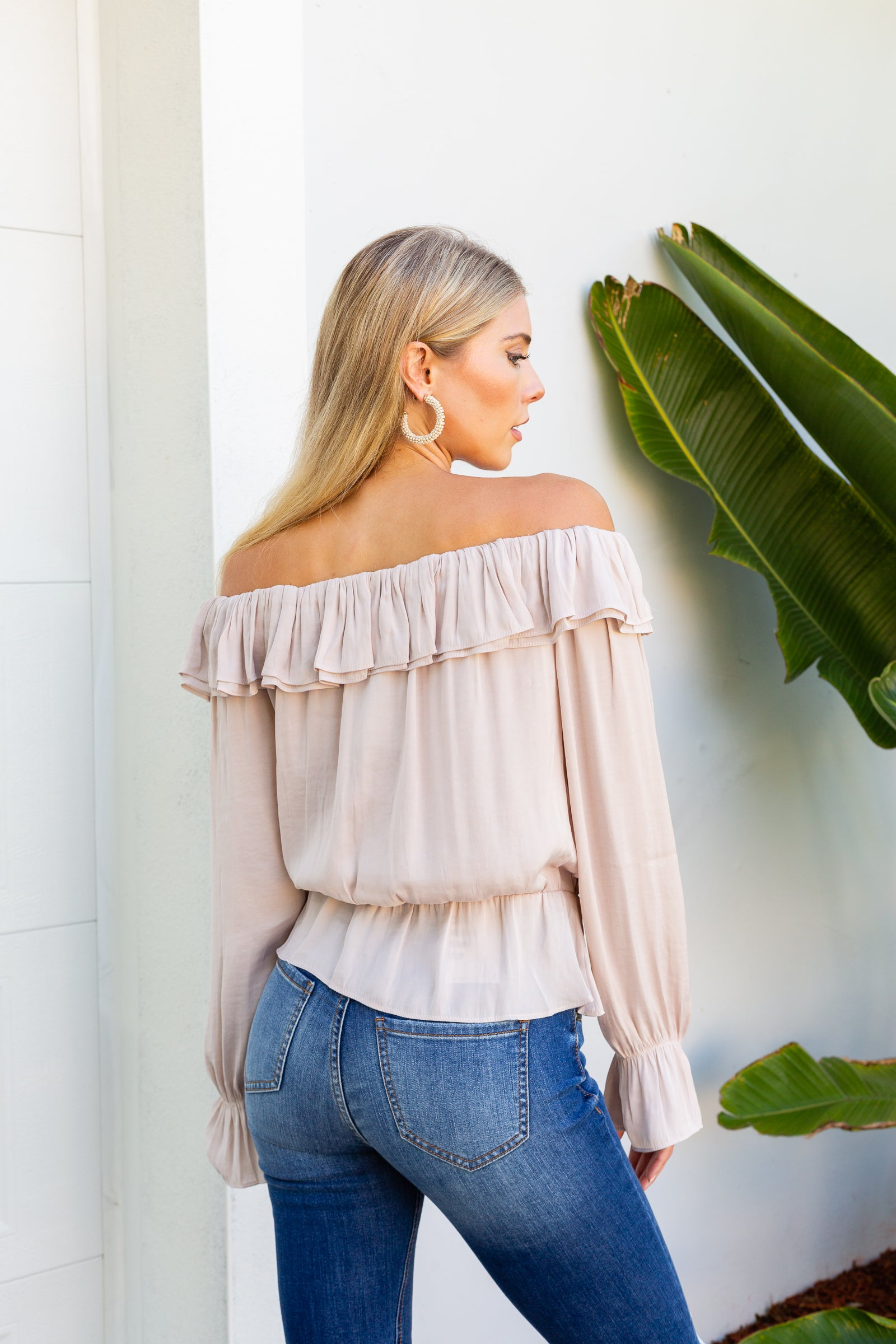 Long elastic ruffle cuffed sleeves attach to a boat neckline with layered ruffle hem on an oversized and loose bodice silhouette and meets an elastic waistband that flares into a peplum style hem.