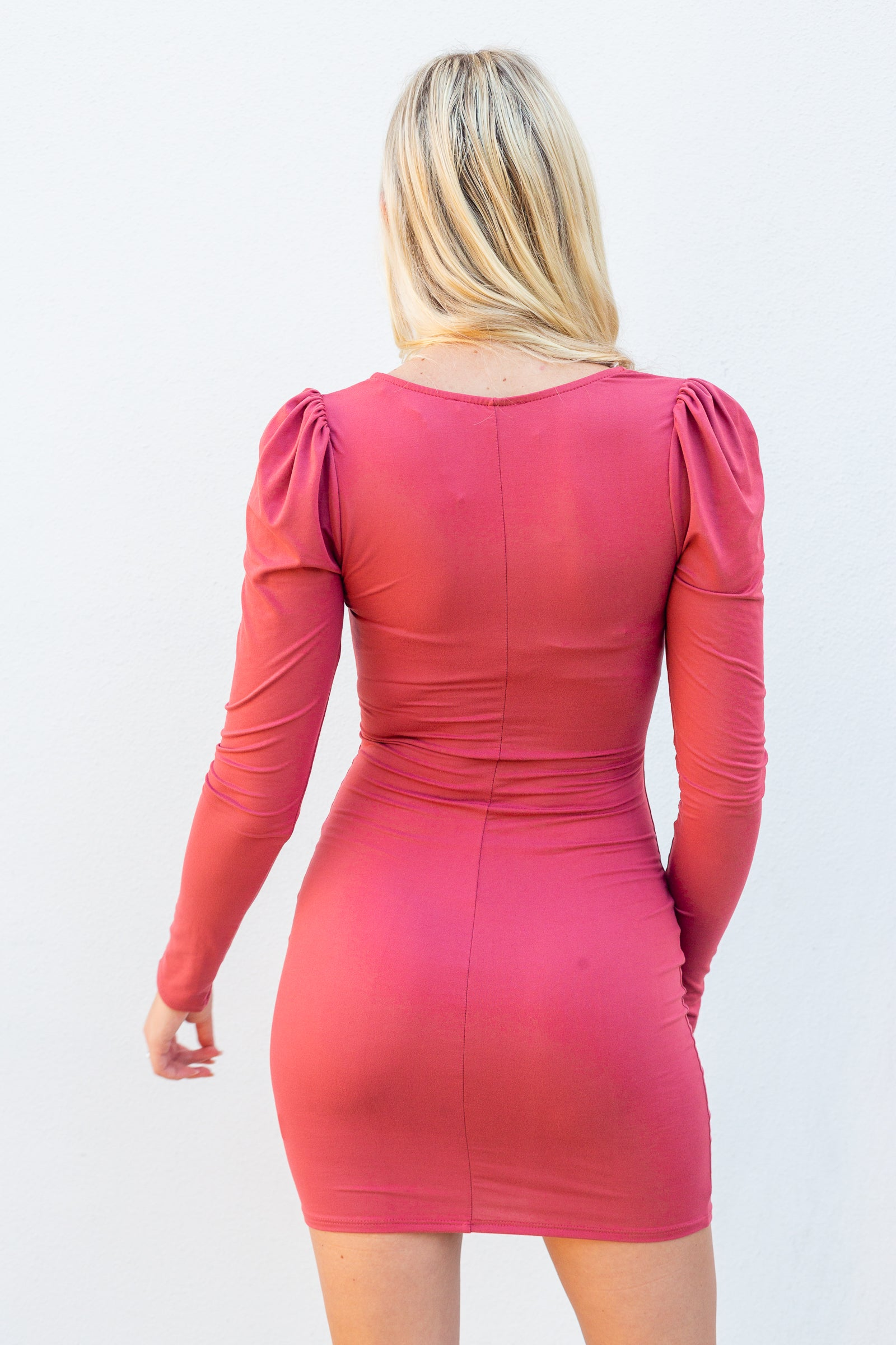 Long fitted sleeves that attach to a v-neckline with a ruched bust bodice and lead to an exposed cut-out midriff and leads to a fitted and hip-hugging skirt.