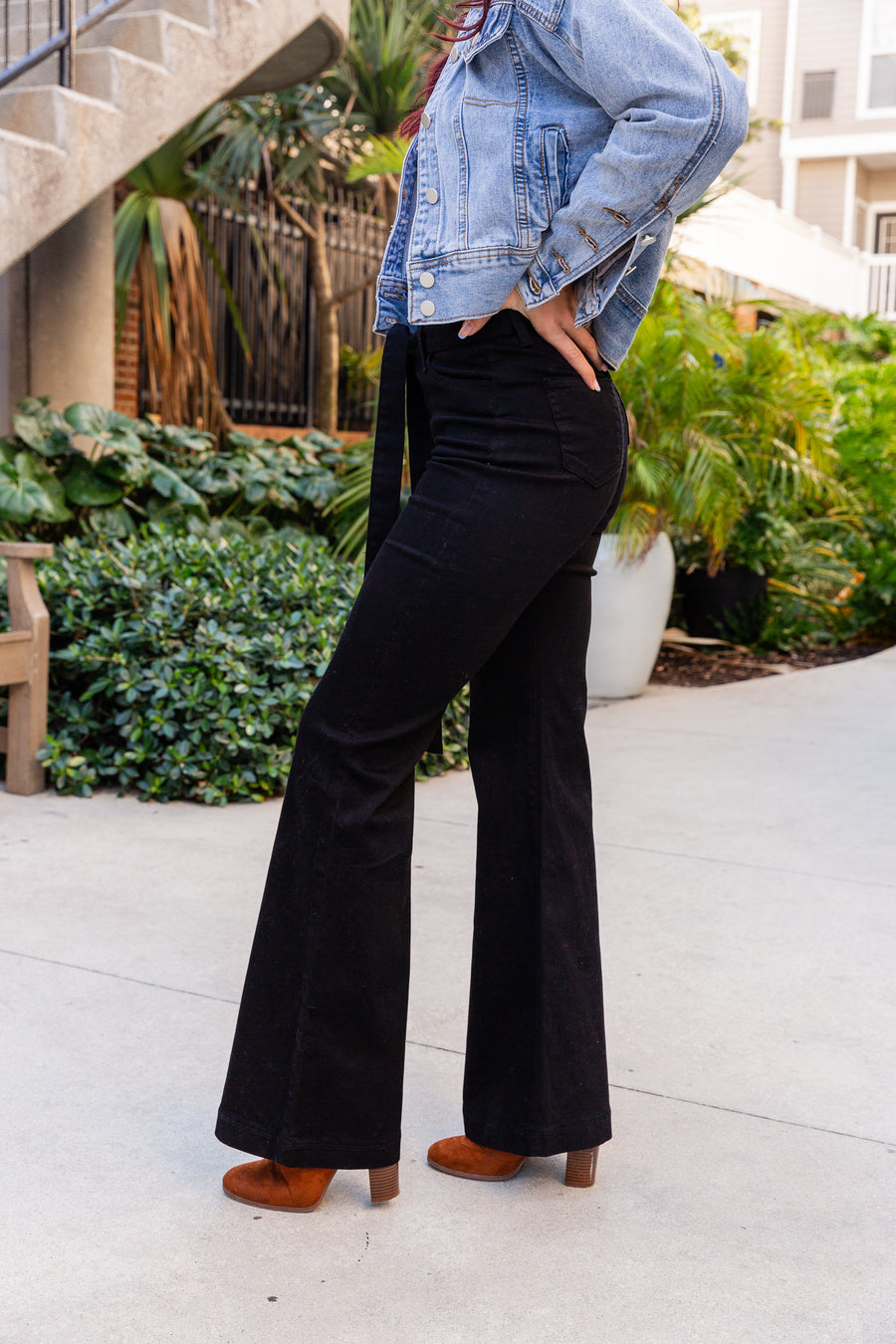 These black pants have a high-rise fitted waist with a zipper fly meeting square side pockets and goes into long flared pant legs with a clean hem.