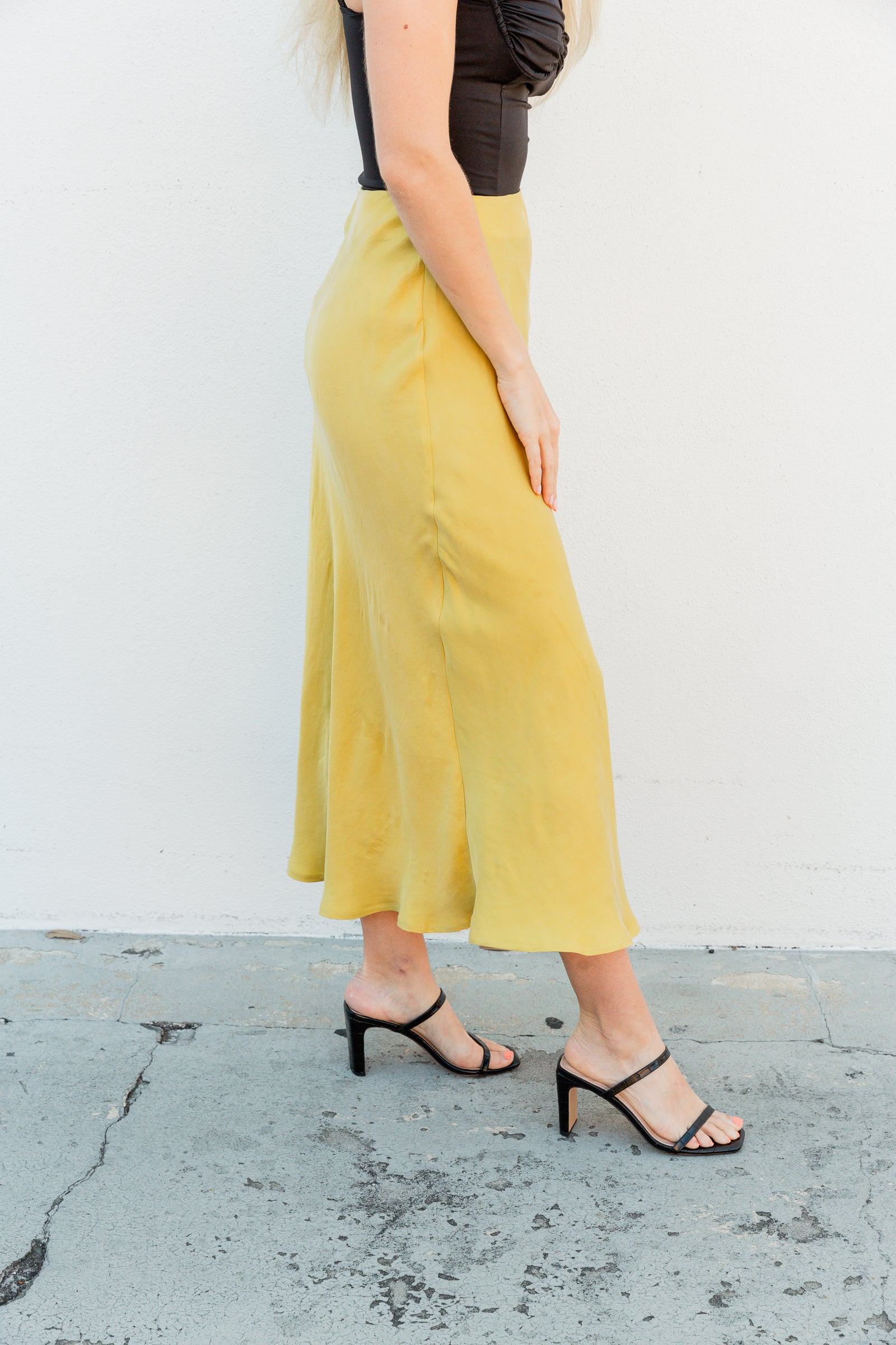 This satiny skirt has a fitted waistband that leads into a fitted then flowy skirt silhouette that meets mid-calf. This midi skirt features a zipper on the side of the skirt.