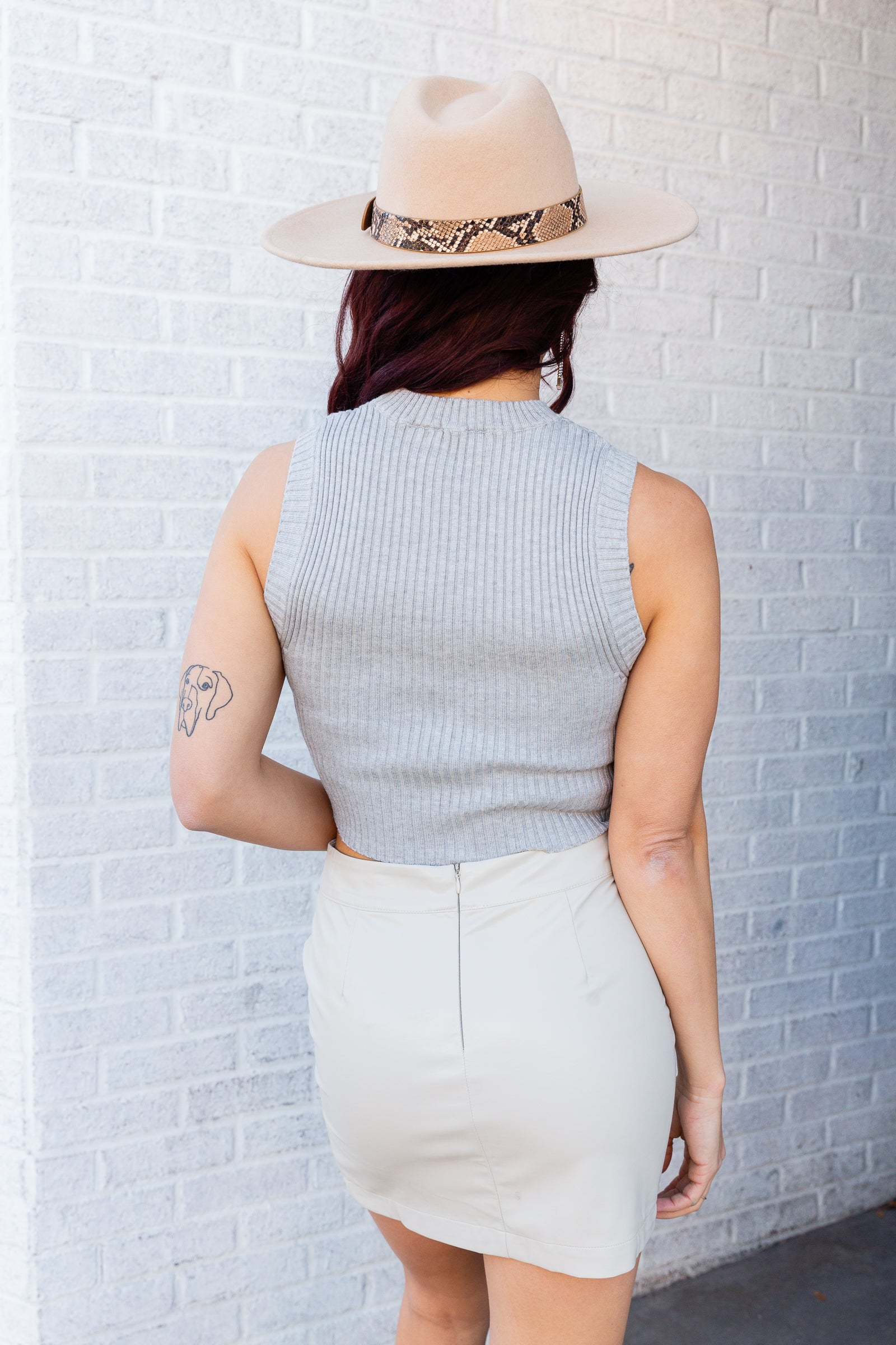 Sleeveless to a mock neckline on a fitted and ribbed knit bodice. Style this chic sweater vest over a collared button-down, with a mini skirt, booties, and a mini handbag.