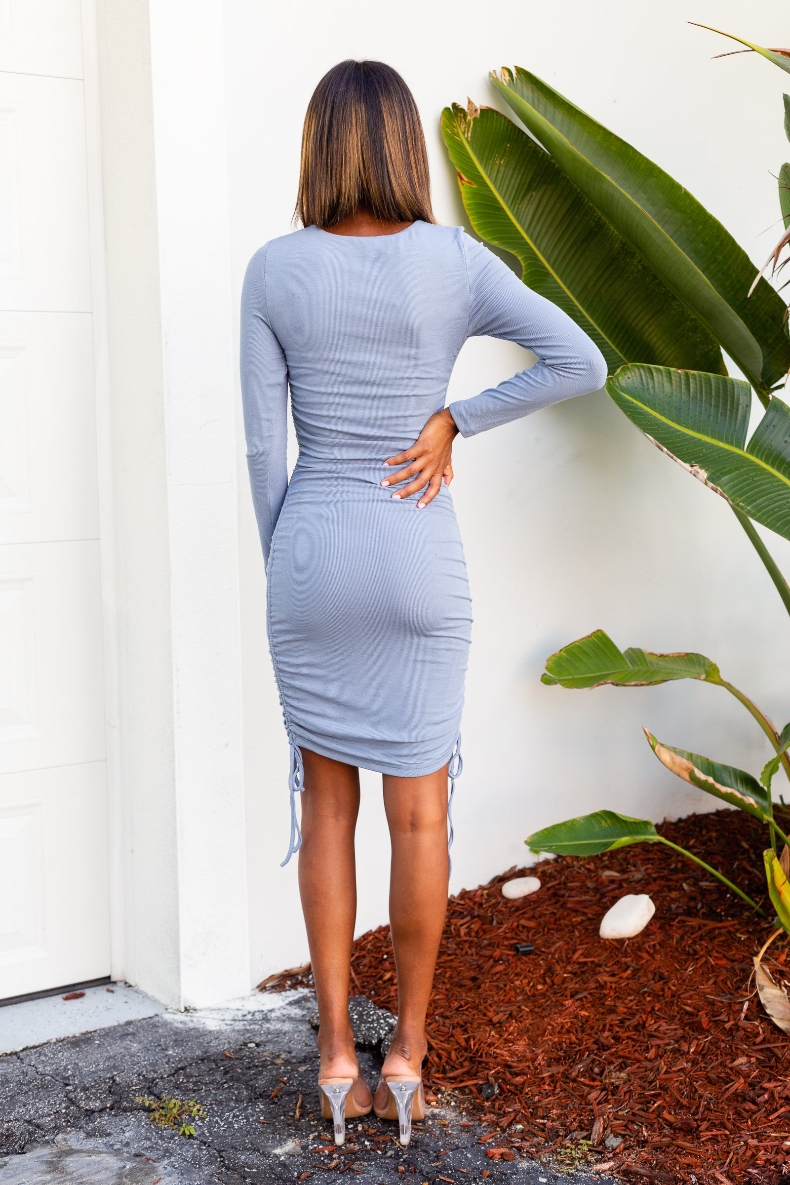 Long fitted sleeves attach to a u-neckline on a fitted and ribbed bodice and go down into a hip-hugging midi skirt with drawstring tied ruched details at the side of the dress.