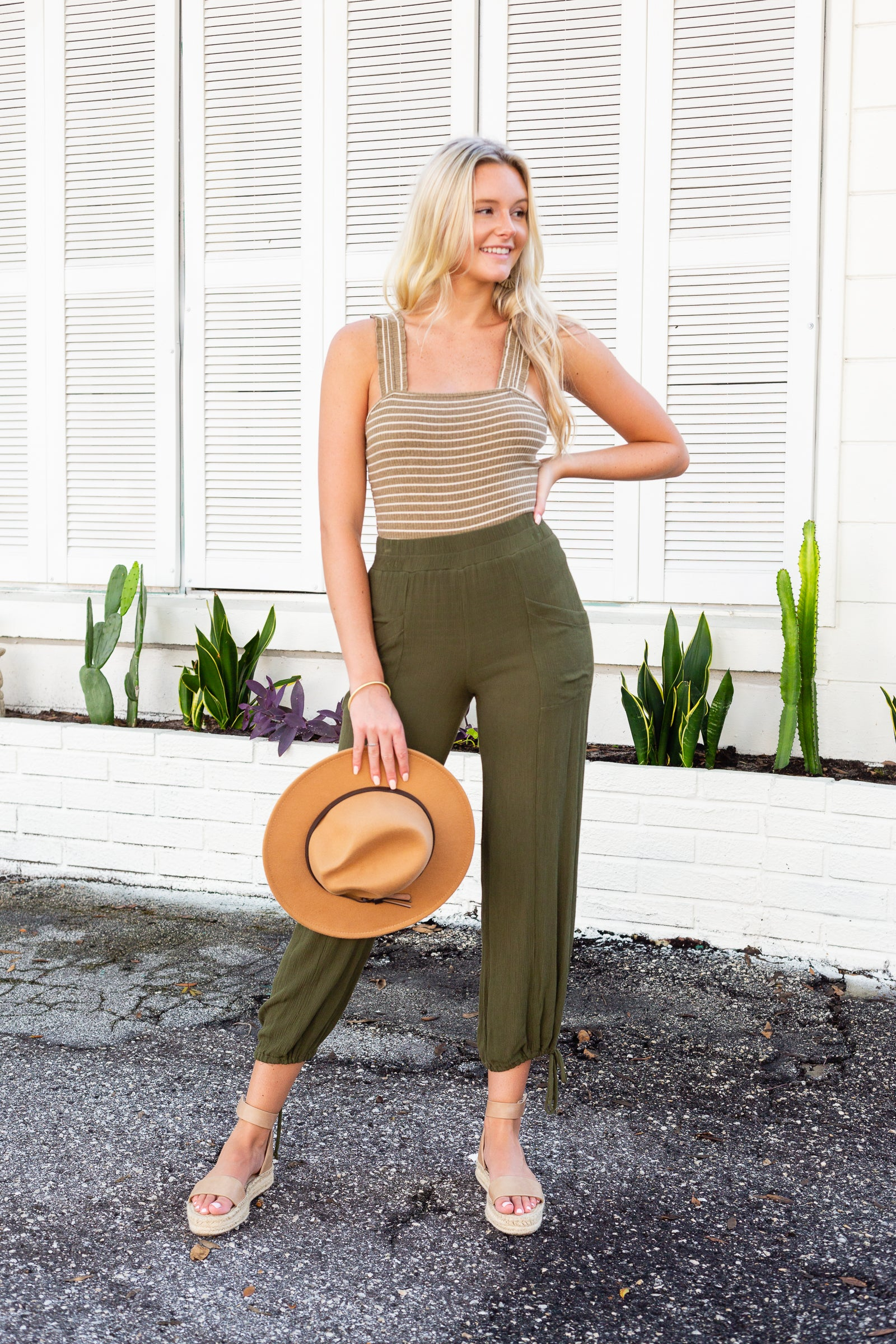 These pants have an elastic waistband and lead to a loose and relaxed fit balloon pants with front pockets and taper into comfortable pant legs with drawstring tied cuffs at the ankles.