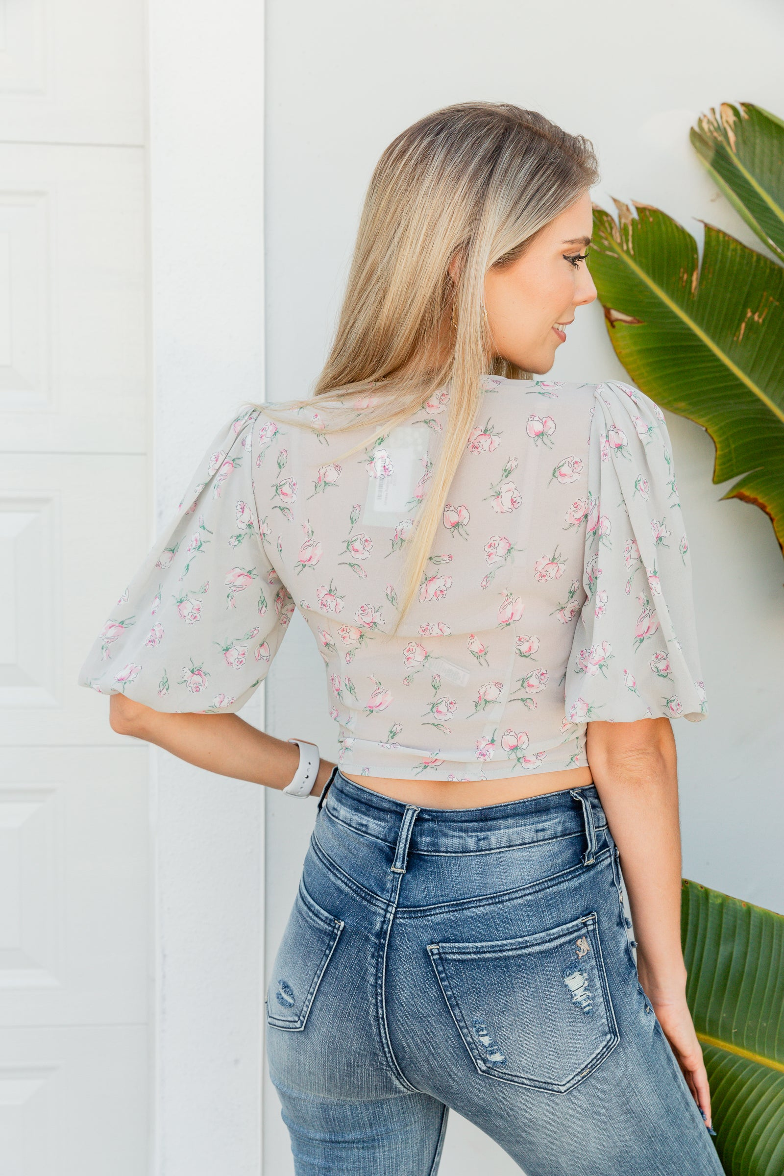Small floral prints cover the fabric of this lightweight top. Mid-length bubble puffed sleeves attach to a v-neckline on a button-down bodice on a cropped and tie-front hem.