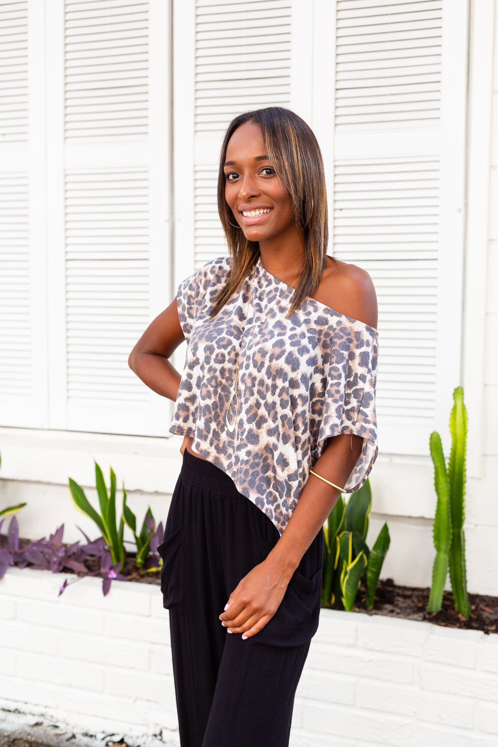 Leopard prints speckle across the fabric of this easy-to-wear t-shirt. Short sleeves attach to a banded u-neckline on an oversized and cropped t-shirt style bodice.