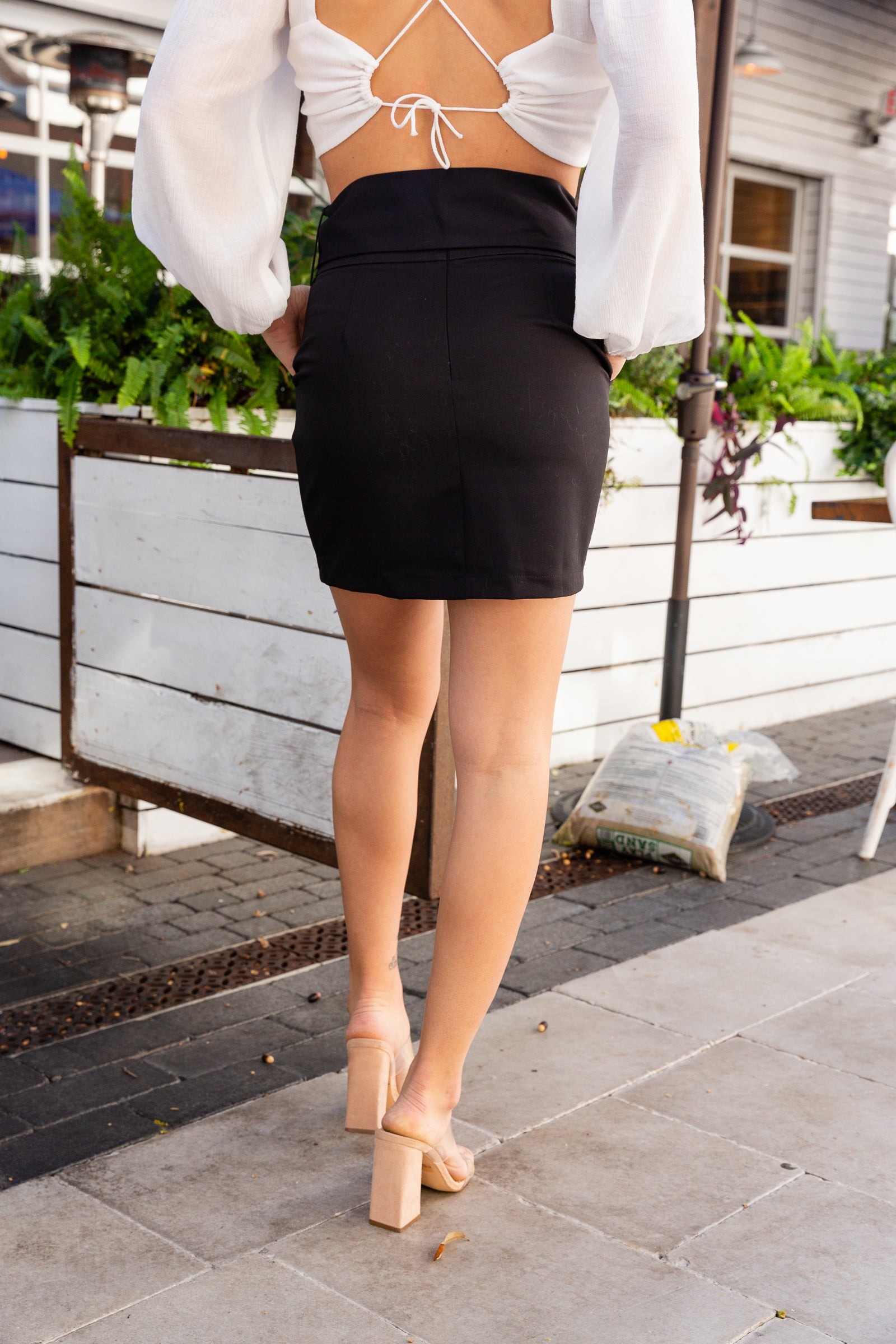 This black skirt has a fitted waistband with an attached fabric belt and rectangle buckle detail that leads to side pockets and goes into a mini-pencil silhouette.