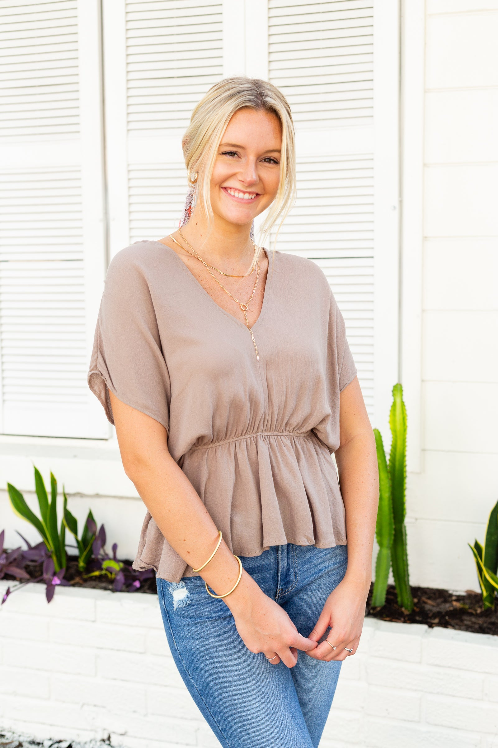 This lightweight top has short sleeves that attach to a v-neckline on an oversized and comfortable bodice meeting an elastic waistband and flow out into a peplum style hem at the bottom.
