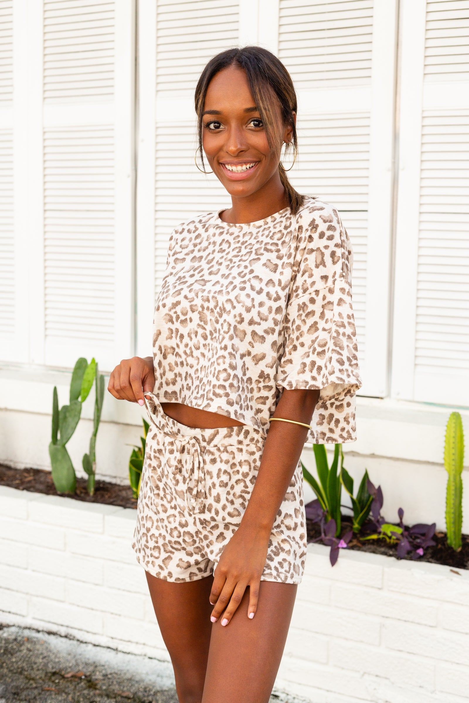 Light leopard spots speckle the fabric of the easy-to-wear lounge top. Short sleeves attach to a banded u-neckline on a comfortable and cropped t-shirt bodice silhouette.