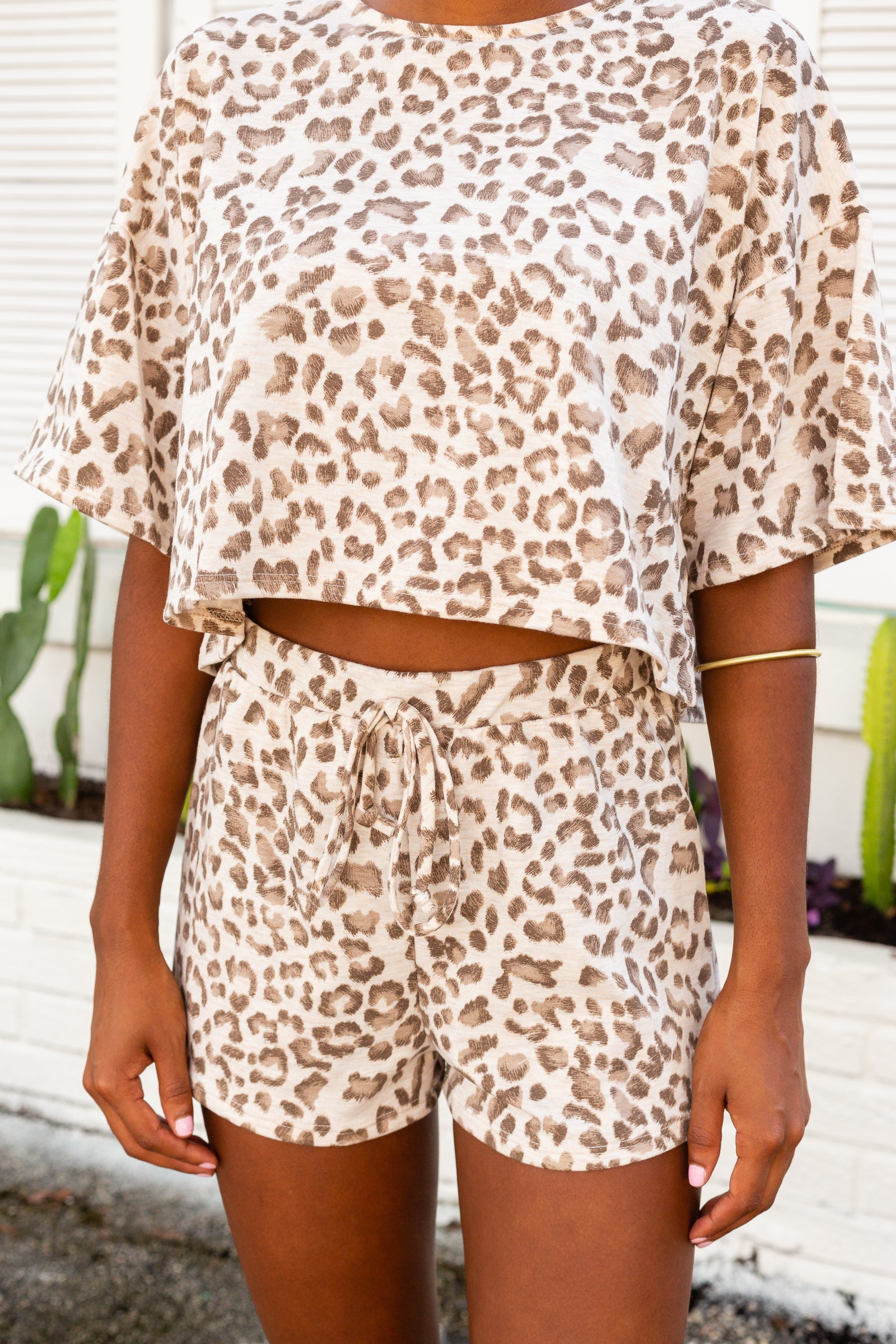 Light leopard spots speckle the fabric of these easy-to-wear shorts. Elastic waistband with a faux drawstring tie leading down to relaxed and comfortable shorts.